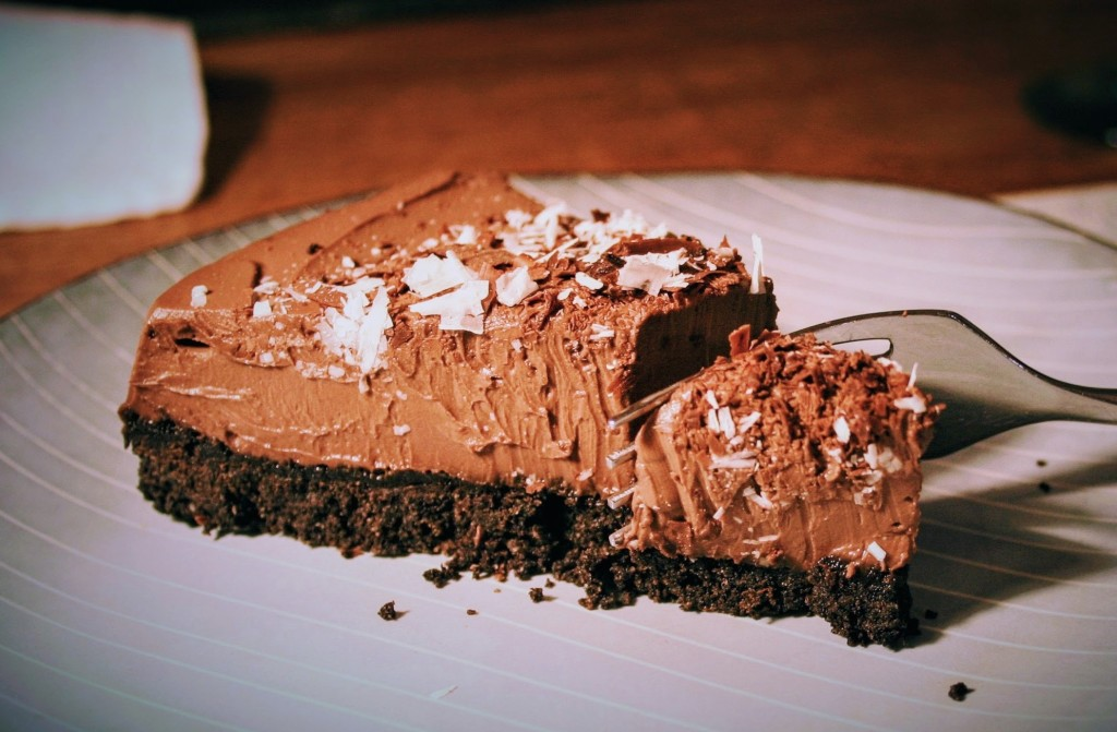 A fork cutting into a smooth and silky vegan chocolate tart which a crumbly chocolate biscuit base.