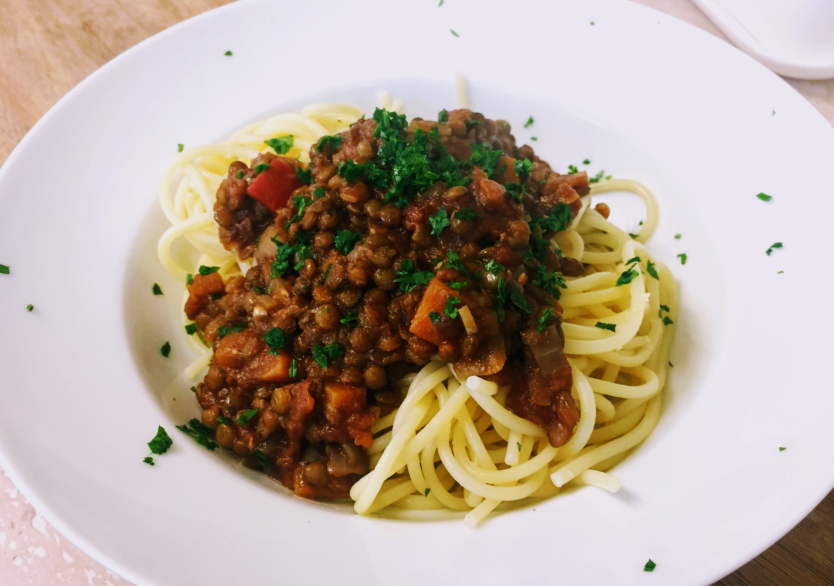 A rich and hearty lentil bolognese, studded with carrots and peppers, piled over a tangled mound of spaghetti and sprinkled with chopped fresh parsley.