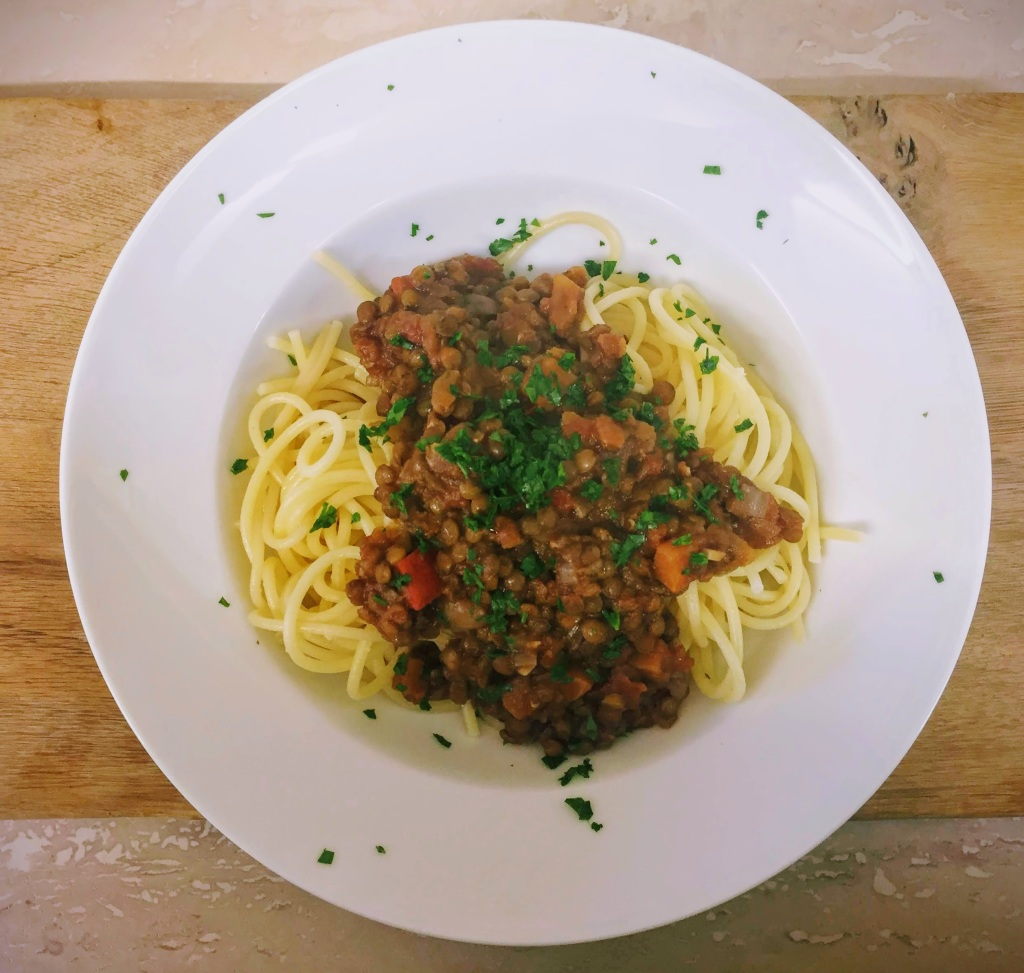The finished vegan lentil bolognese, which is thick and rich, is heaped over spools of spaghetti and finished with some chopped parsley.