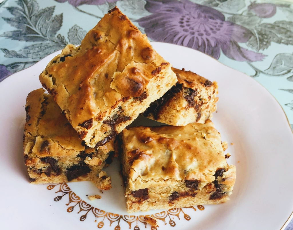 A pile of soft and squidgy vegan and gluten-free blondies. They are golden brown on top and fudgy in the centre, with dark chocolate chips.