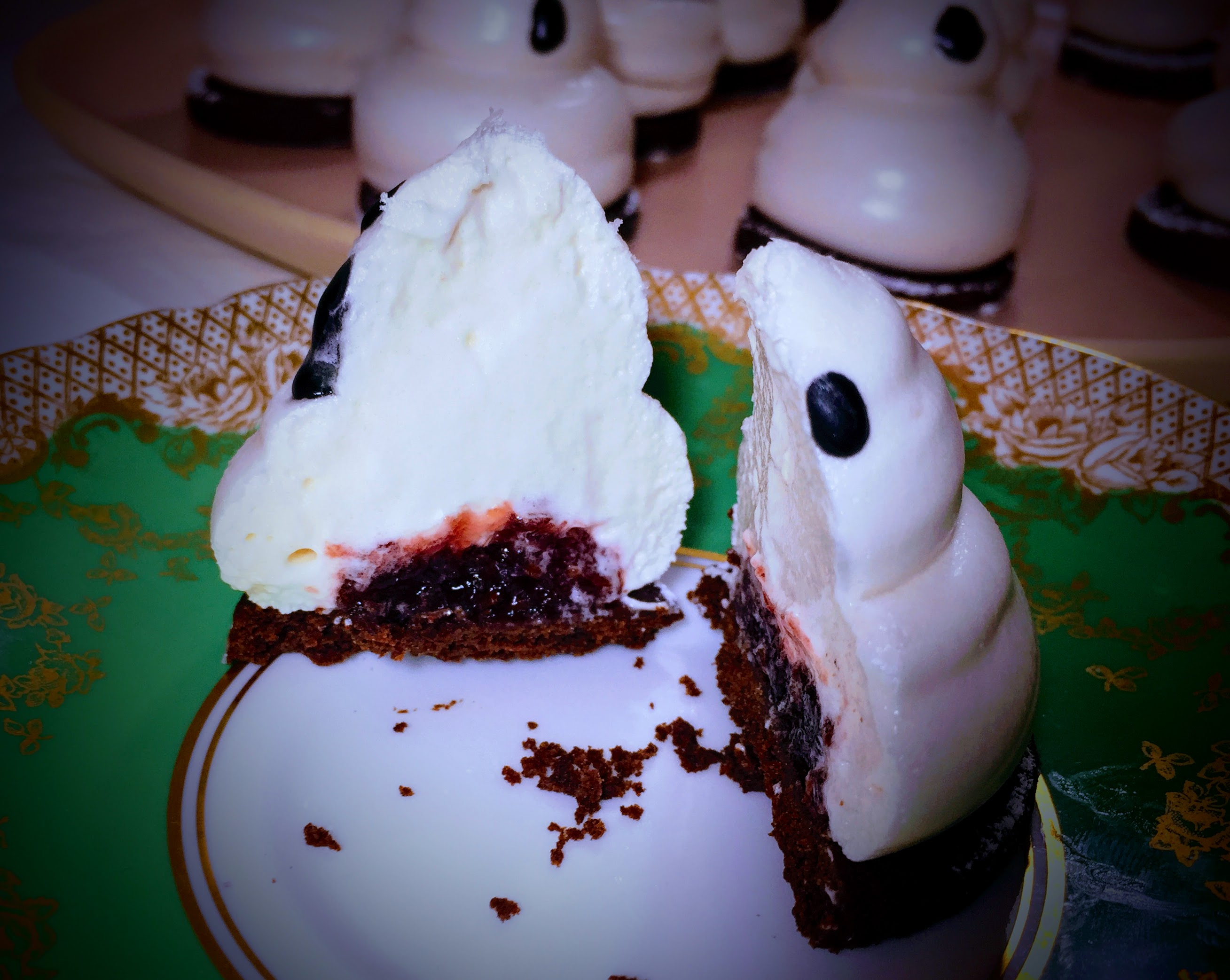 A vegan marshmallow ghost biscuit cut in two. The marshmallow is sliced smoothly to reveal a red jam centre.