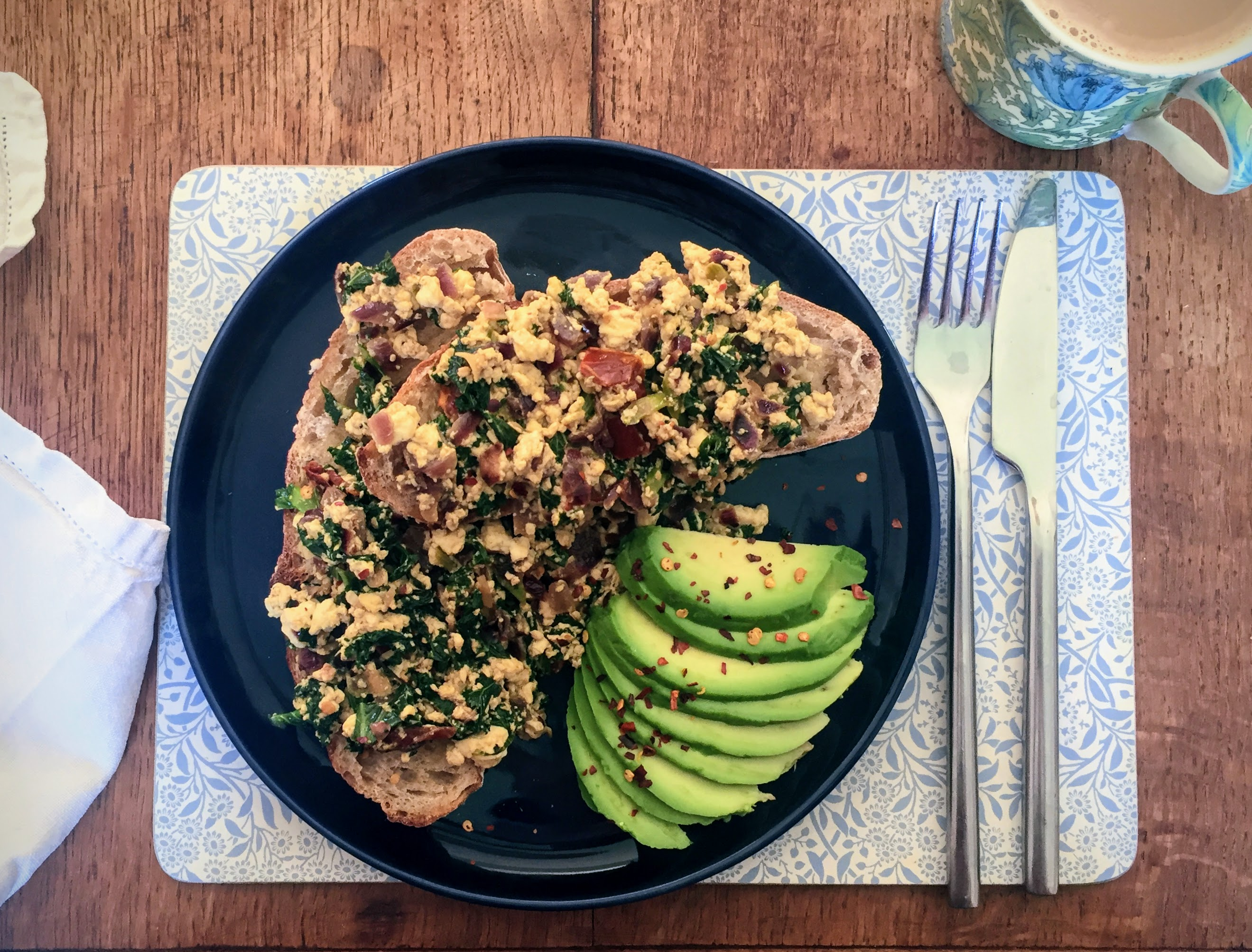 Tofu scramble with sun-dried tomato  and kale, piled on two slices of toasted sourdough, with finely sliced avocado on the side. It is on a dark navy blue plate, and photographed from above, with a napkin and cup of coffee in the corners of the picture.