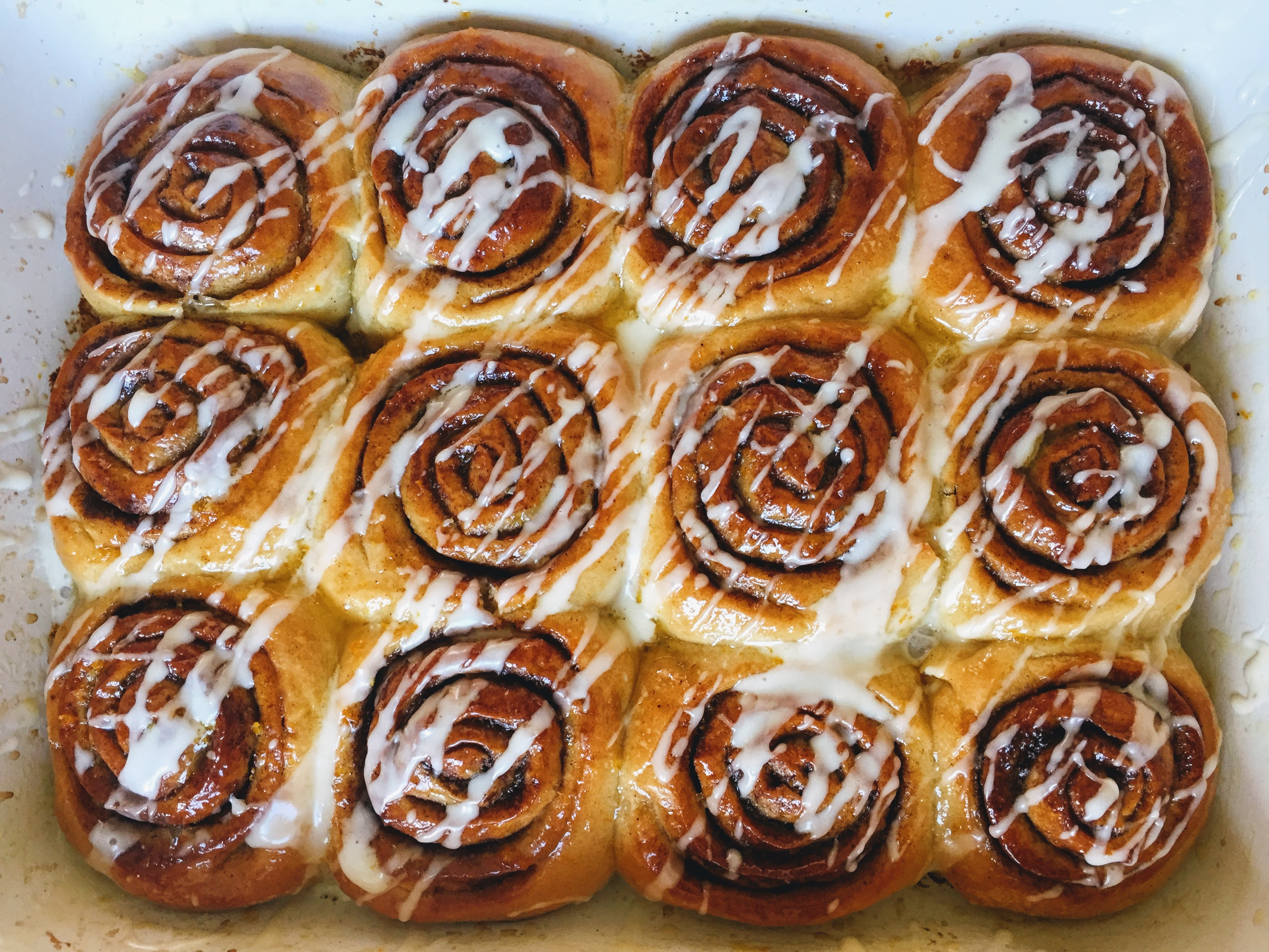 The cinnamon rolls, still in their dish. The rolls are merged together and have a distinct swirl of sweet cinnamon mixture throughout. The rolls are shiny and drizzled with stripes of white icing.