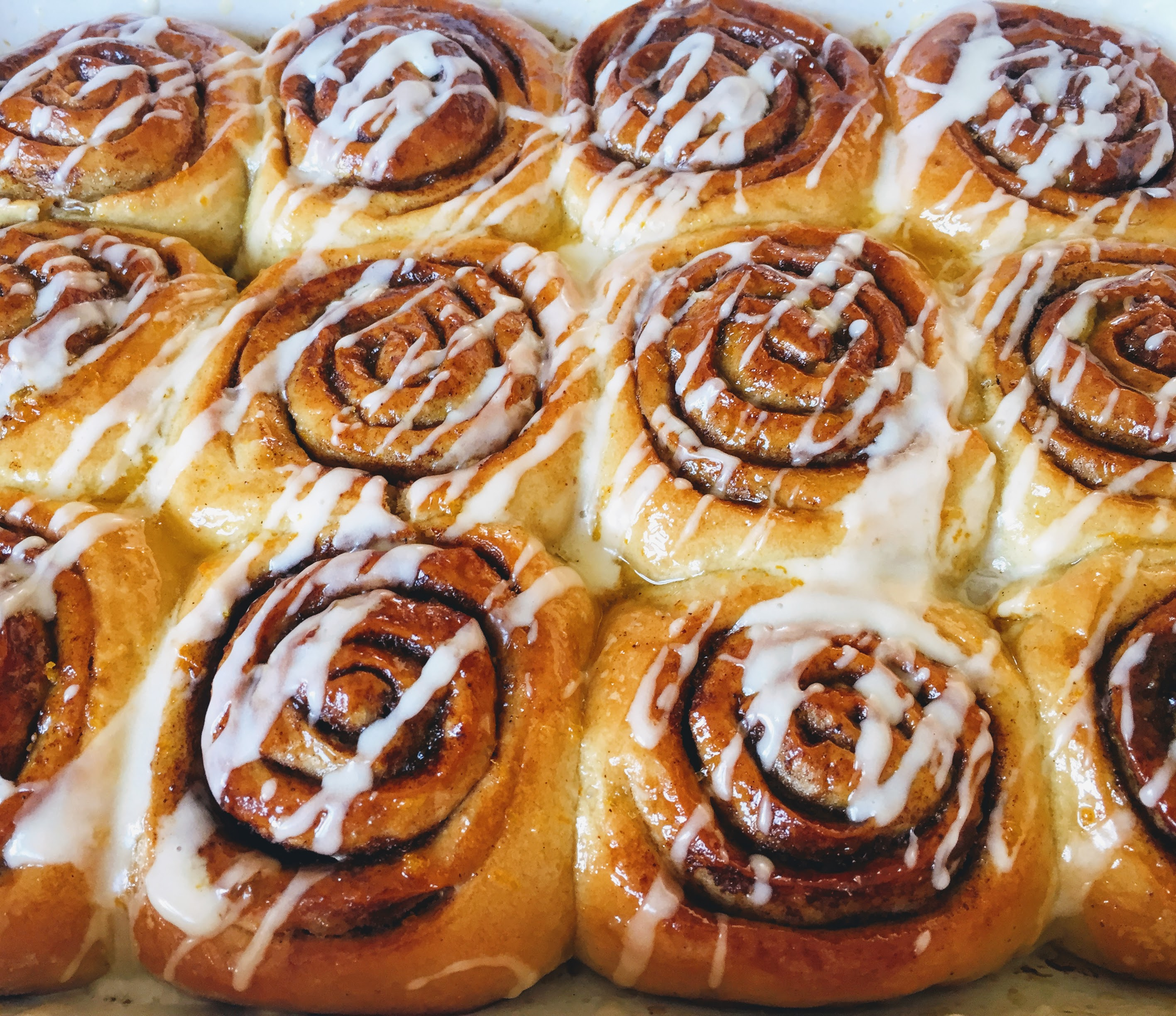 A close-up of the cinnamon rolls, glossy and sticky with the glaze and drizzled in white, orange-flavoured icing.