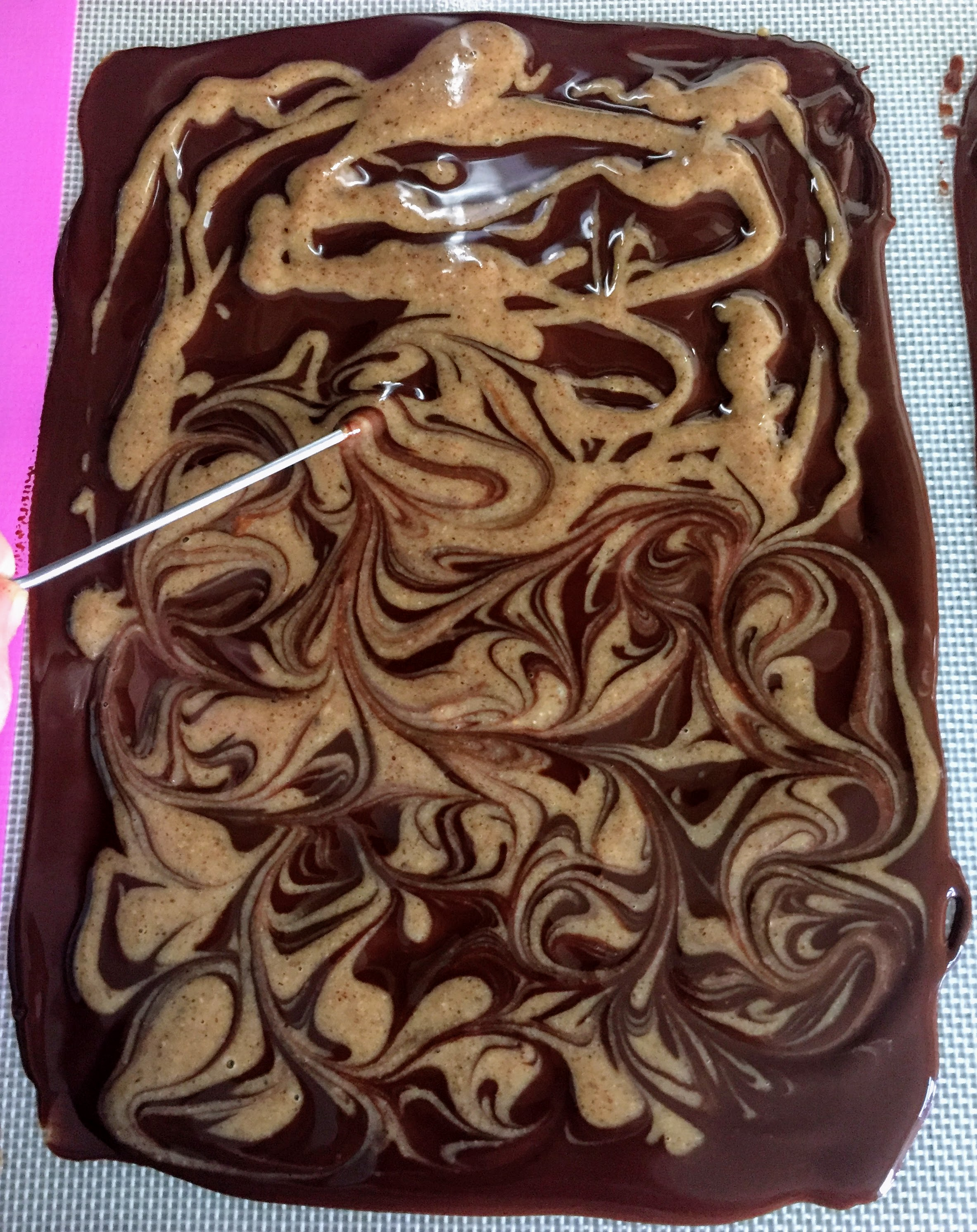 A rectangle of melted dark chocolate, spread on a baking tray and drizzled with almond butter mixture. The top half shows the almond butter roughly drizzled, and the bottom half shows the marbled effect when a skewer is run through the chocolate and almond mixture.