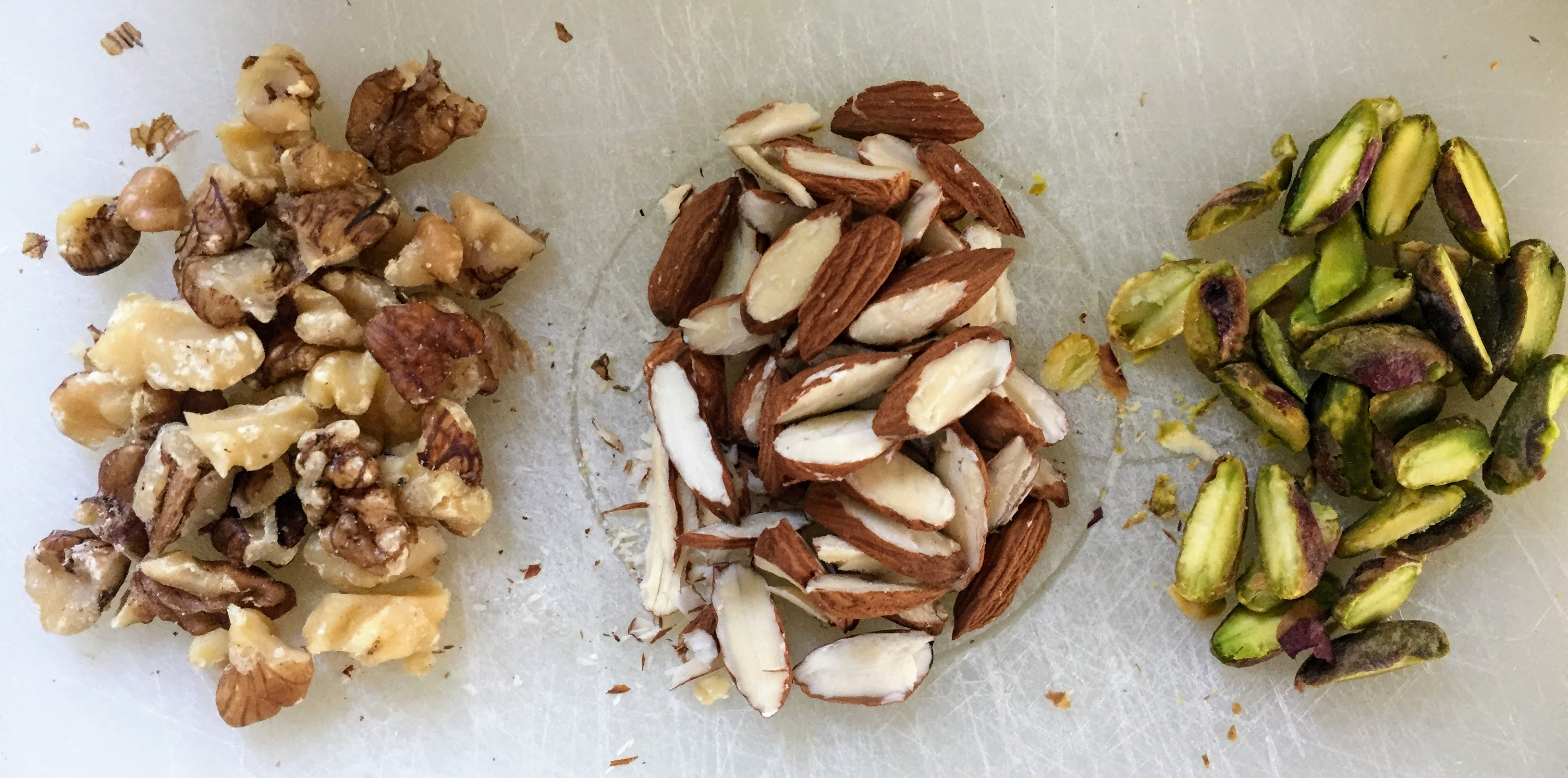 Three small piles of chopped walnuts, slivered almonds, and halved pistachios.
