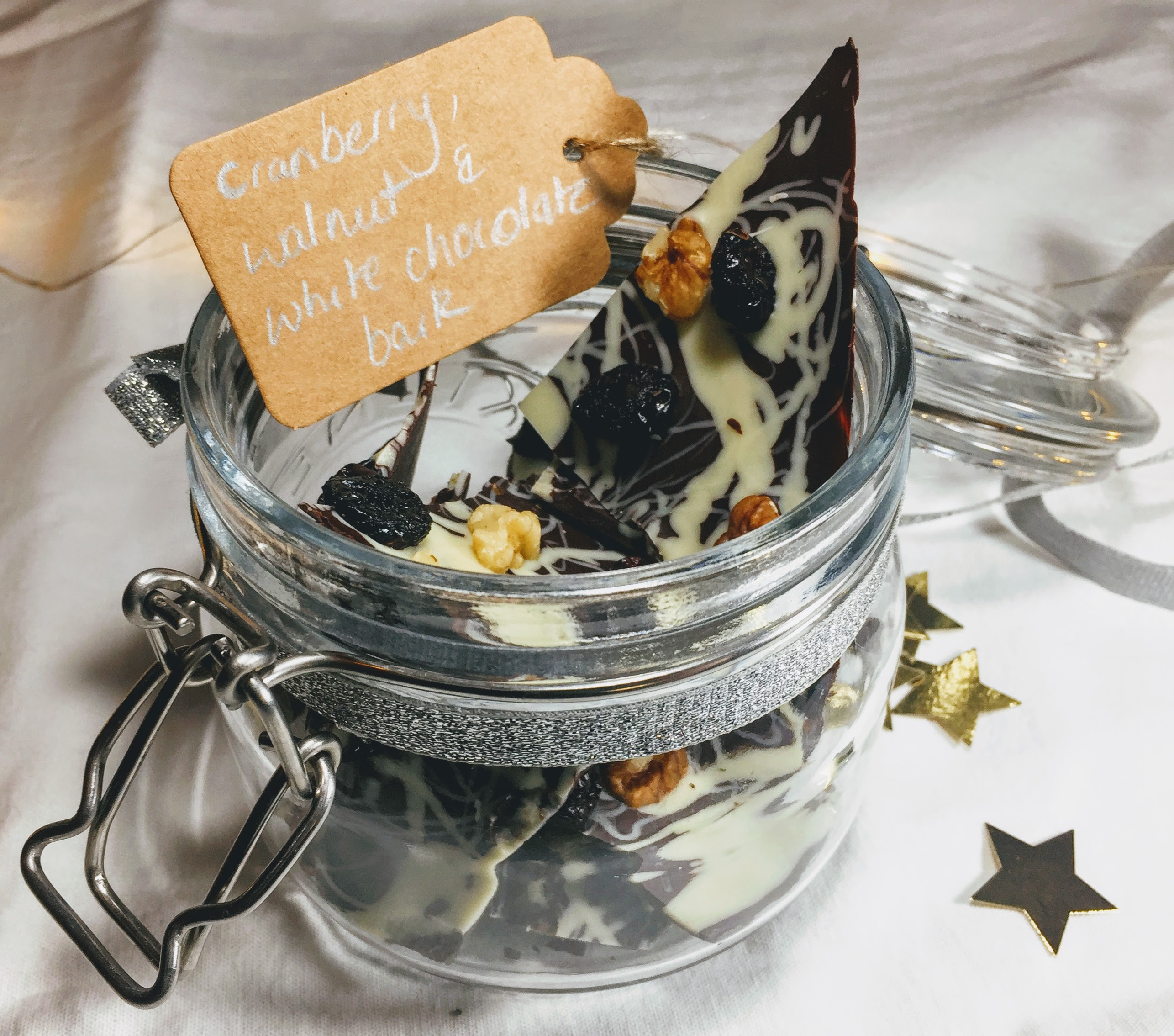 A small glass kilner jar filled with shards of chocolate bark. There jar has a glittery silver ribbon and a brown paper tag that reads 'Cranberry, walnut & white chocolate bark' handwritten in silver pen.