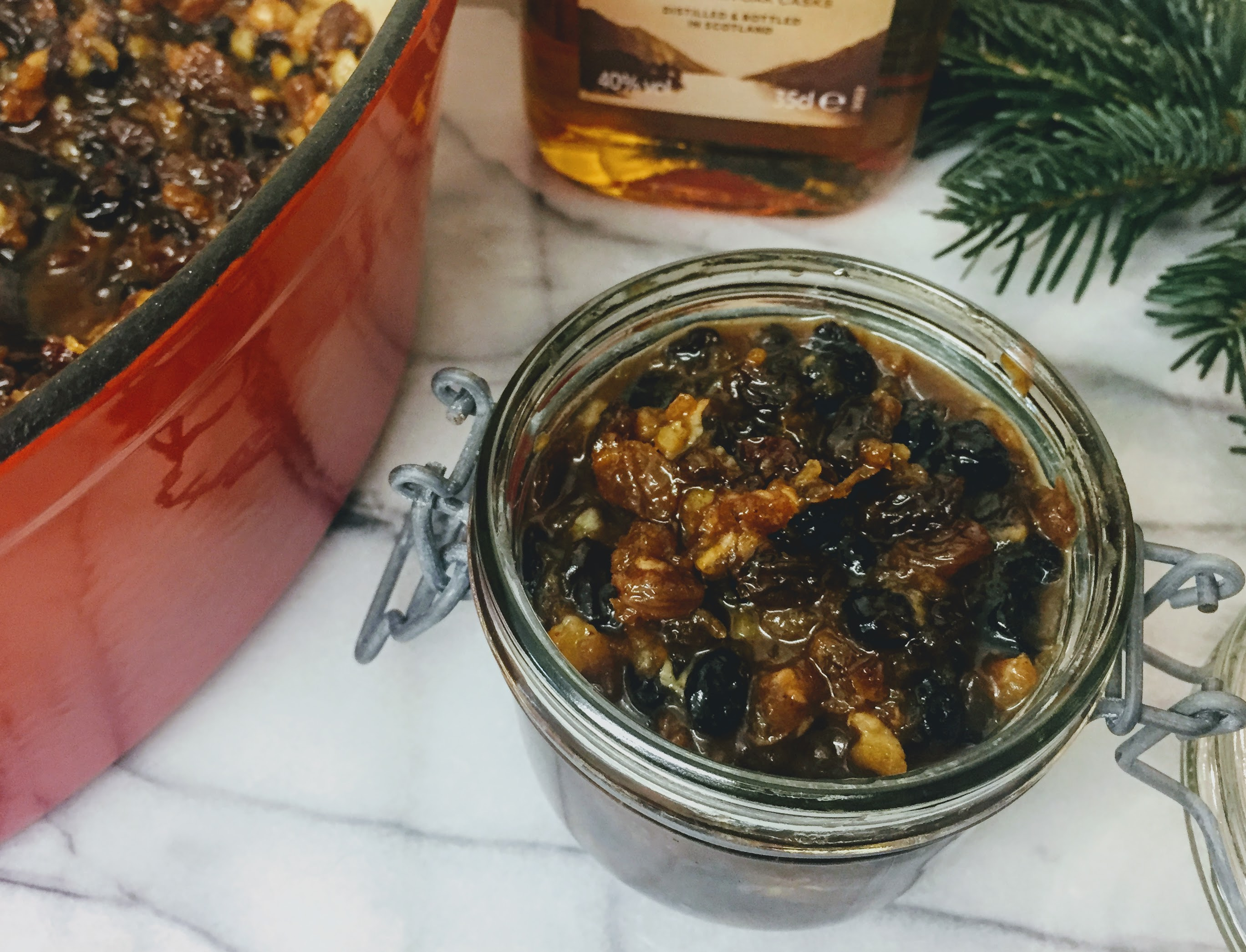 A small glass jar packed with mincemeat; the dried fruit is slightly plump from the liquid and is dark and glistening. The pan with the remaining mincemeat, a half bottle of whiskey and a pine sprig surround the jar.