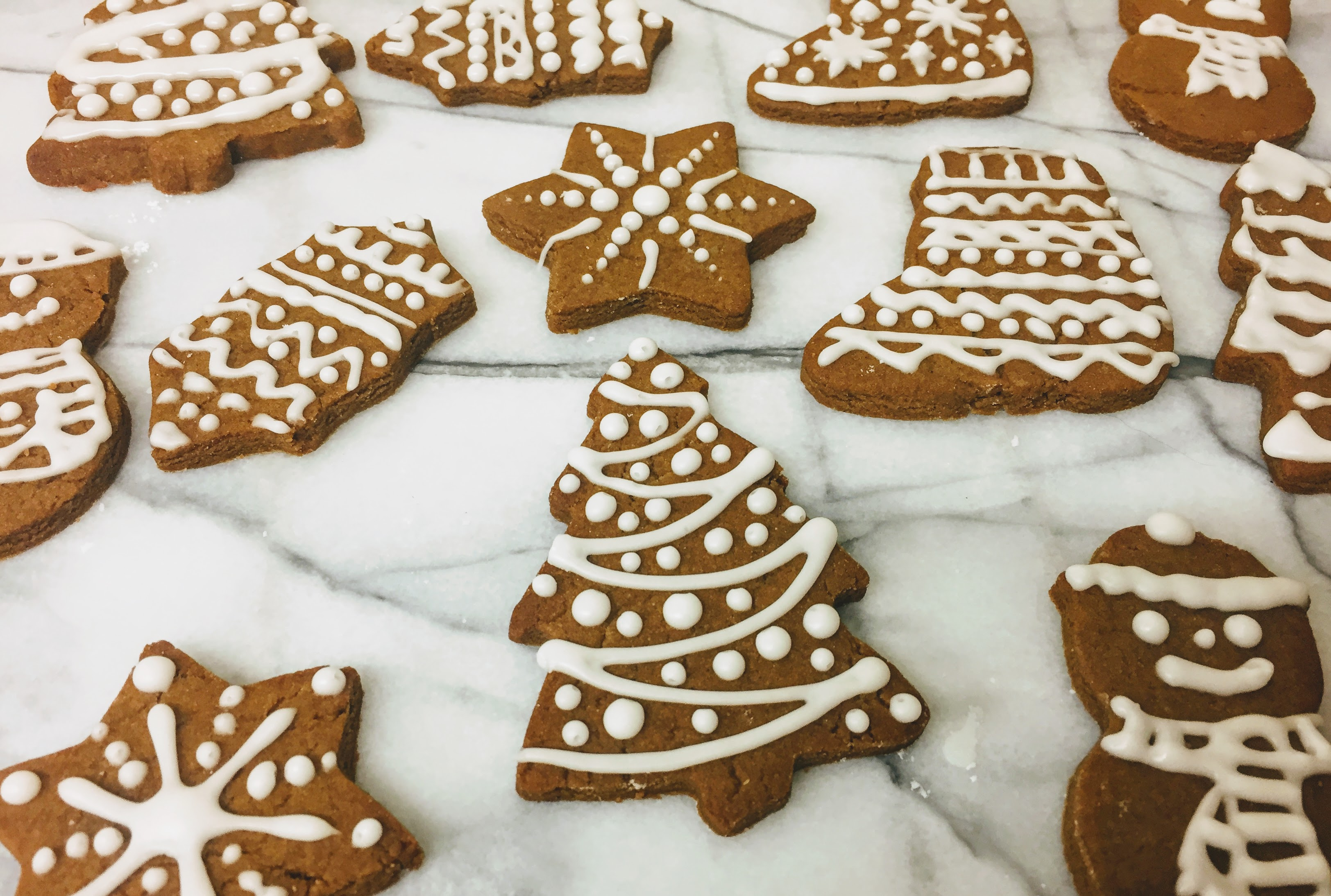 A side view of the gingerbread biscuits, which are about half a centimeter thick. A christmas tree is at the front of the picture with icing piped like tinsel and baubles.