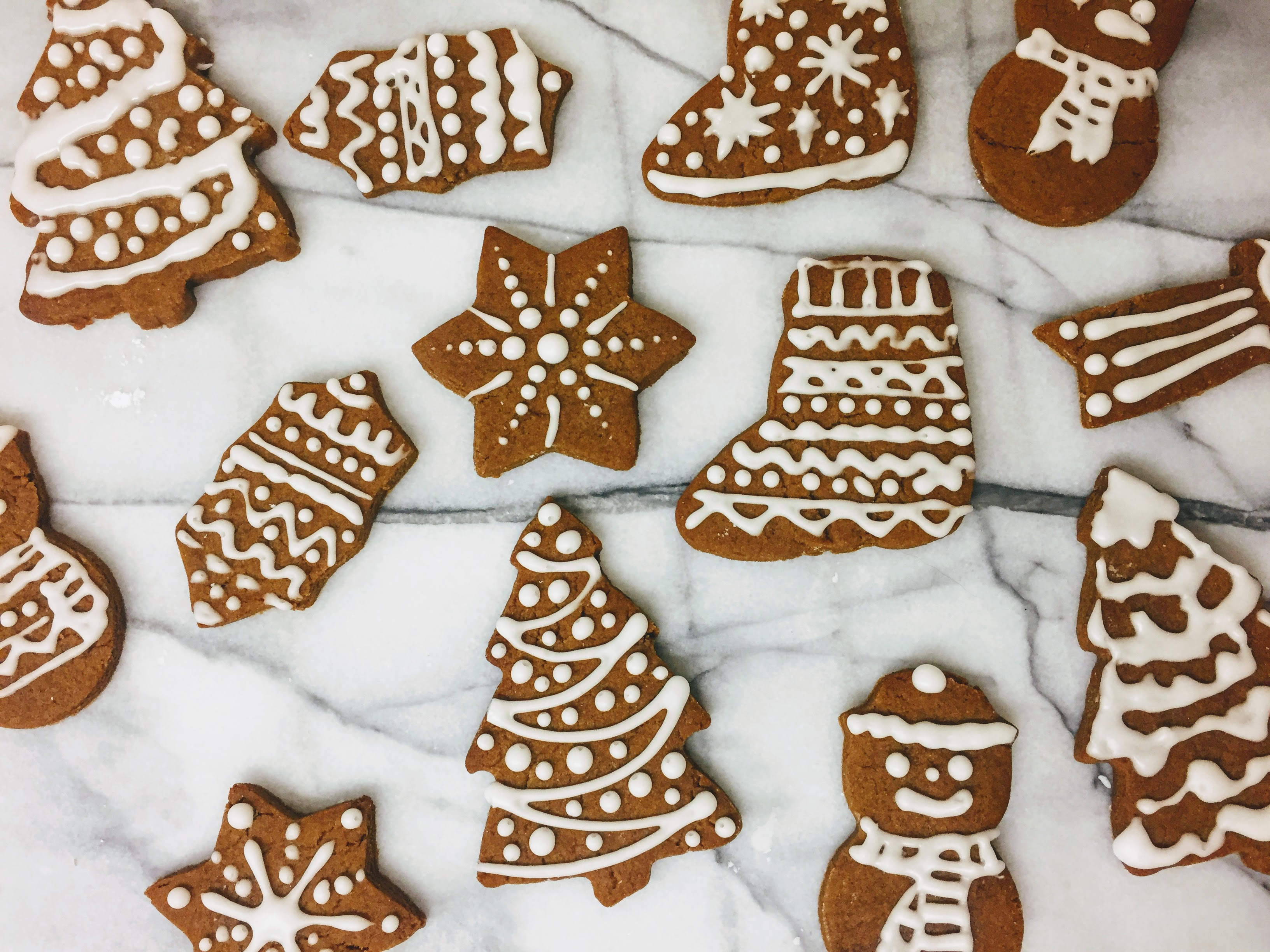 An aerial view of the gingerbread biscuits laid out on a marble board, shaped like stars, christmas trees, stockings, snowmen and holly. The biscuits are dark golden brown and are decorated with piped bright white icing.