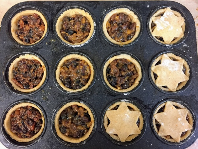 A cupcake tray - each hole is lined with pastry and filled with mincemeat, up to the rim. A few have their star-shaped lids pressed on.
