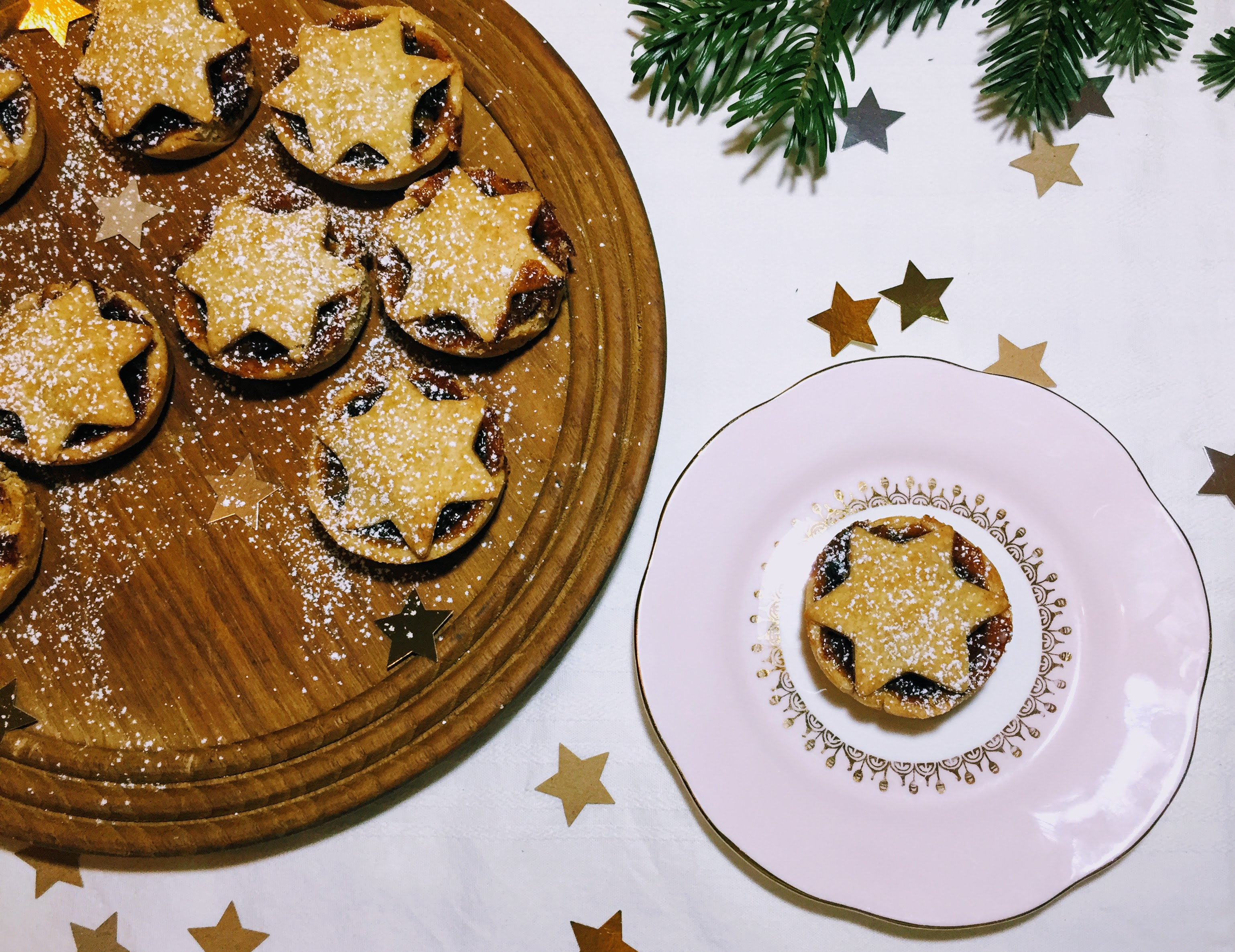 Mince pies on a wooden board, with star-shaped lids of golden pastry, dusted with icing sugar. A single pie is next to the others on a pink plate. There are some pine leaves in the top right hand corner and some star-shaped confetti scattered over a white table cloth.