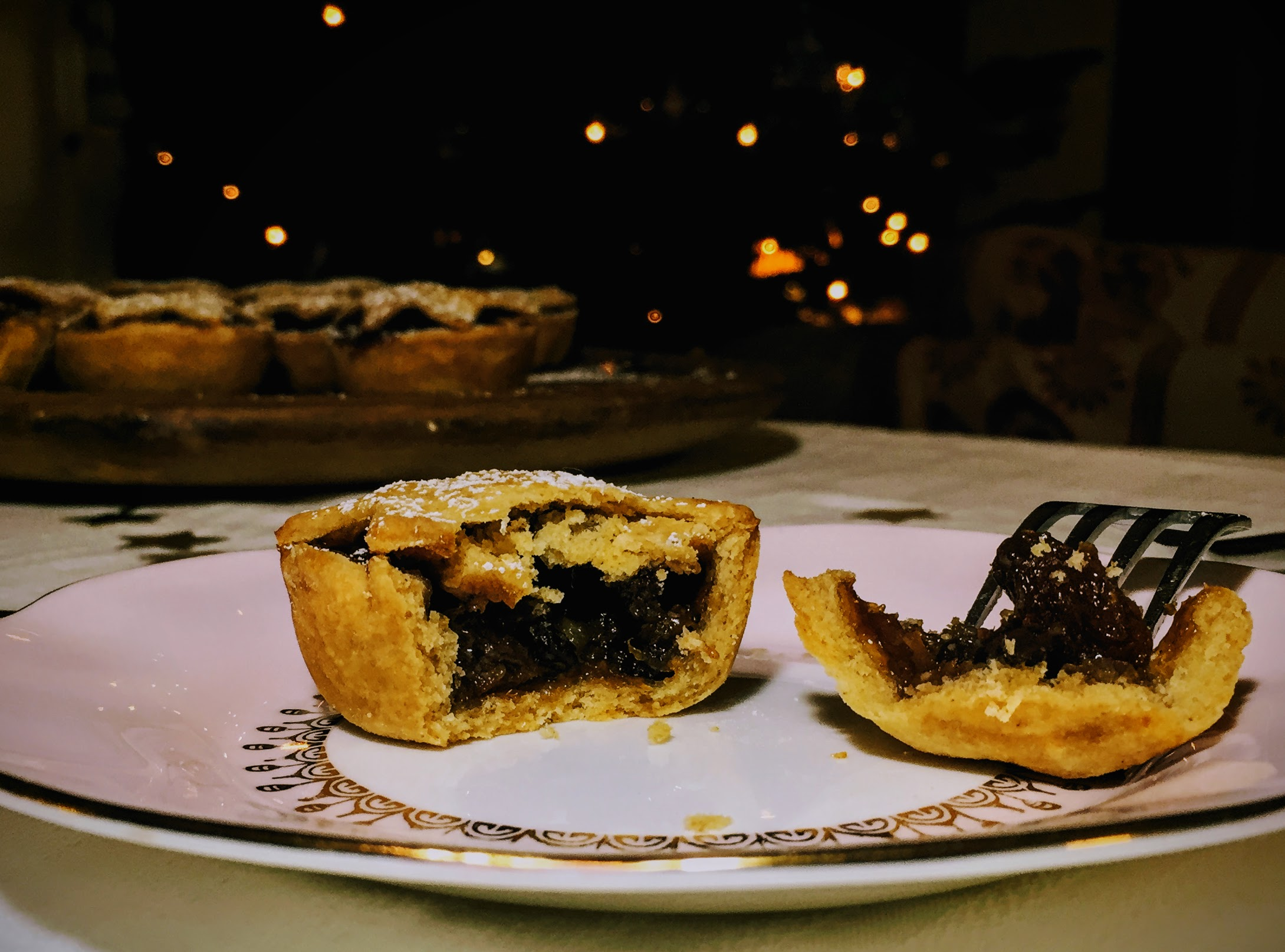 A mice pie, cut open to reveal the dark and glistening mincemeat filling. The pastry is golden, flakey and crumbling. The rest of the mince pies are on a board behind, and Christmas lights sparkle in the background.