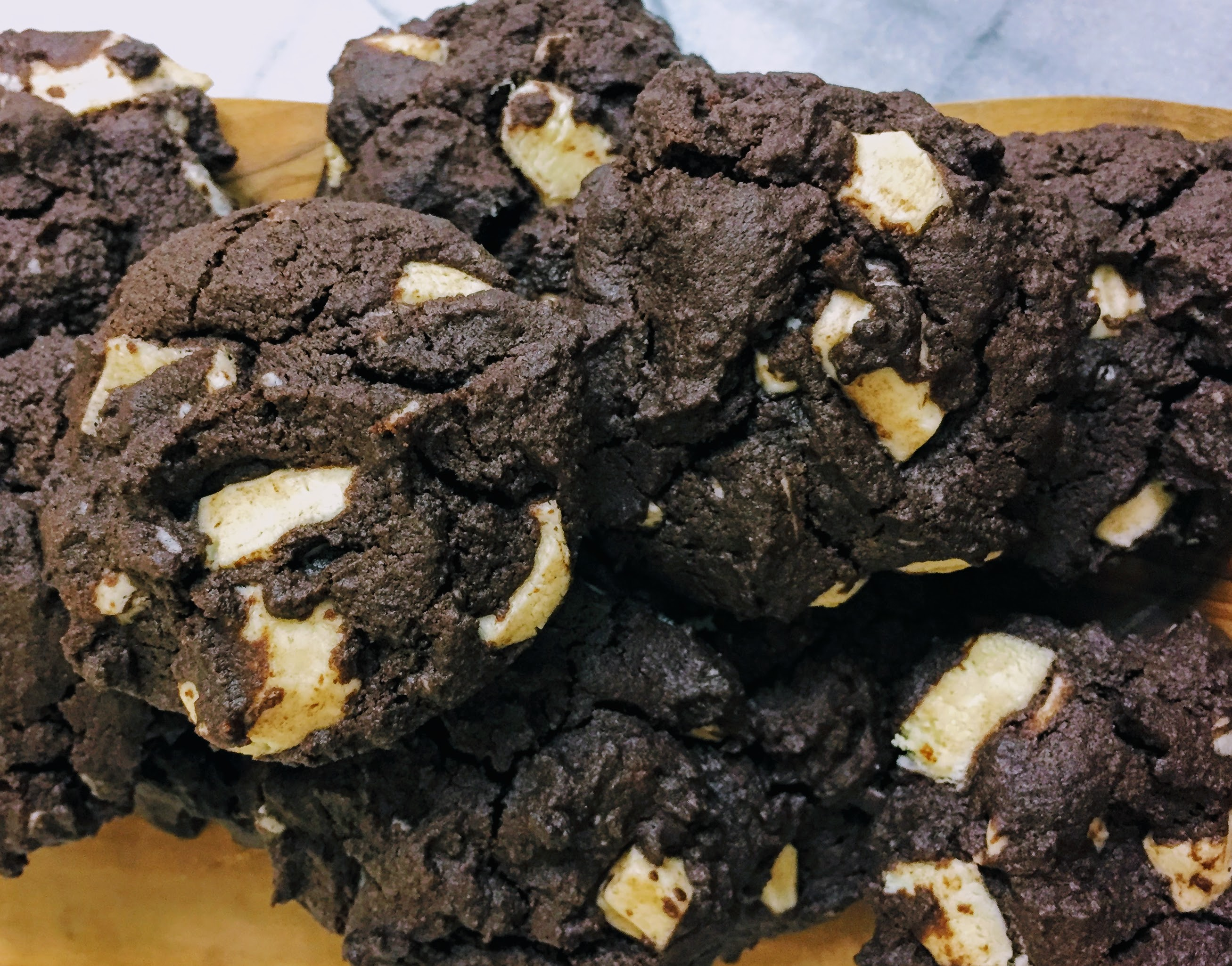A pile of double chocolate buckwheat brownie cookies, photographed from above. The cookies are a rich dark brown, with chunks of white chocolate peaking through the surface.