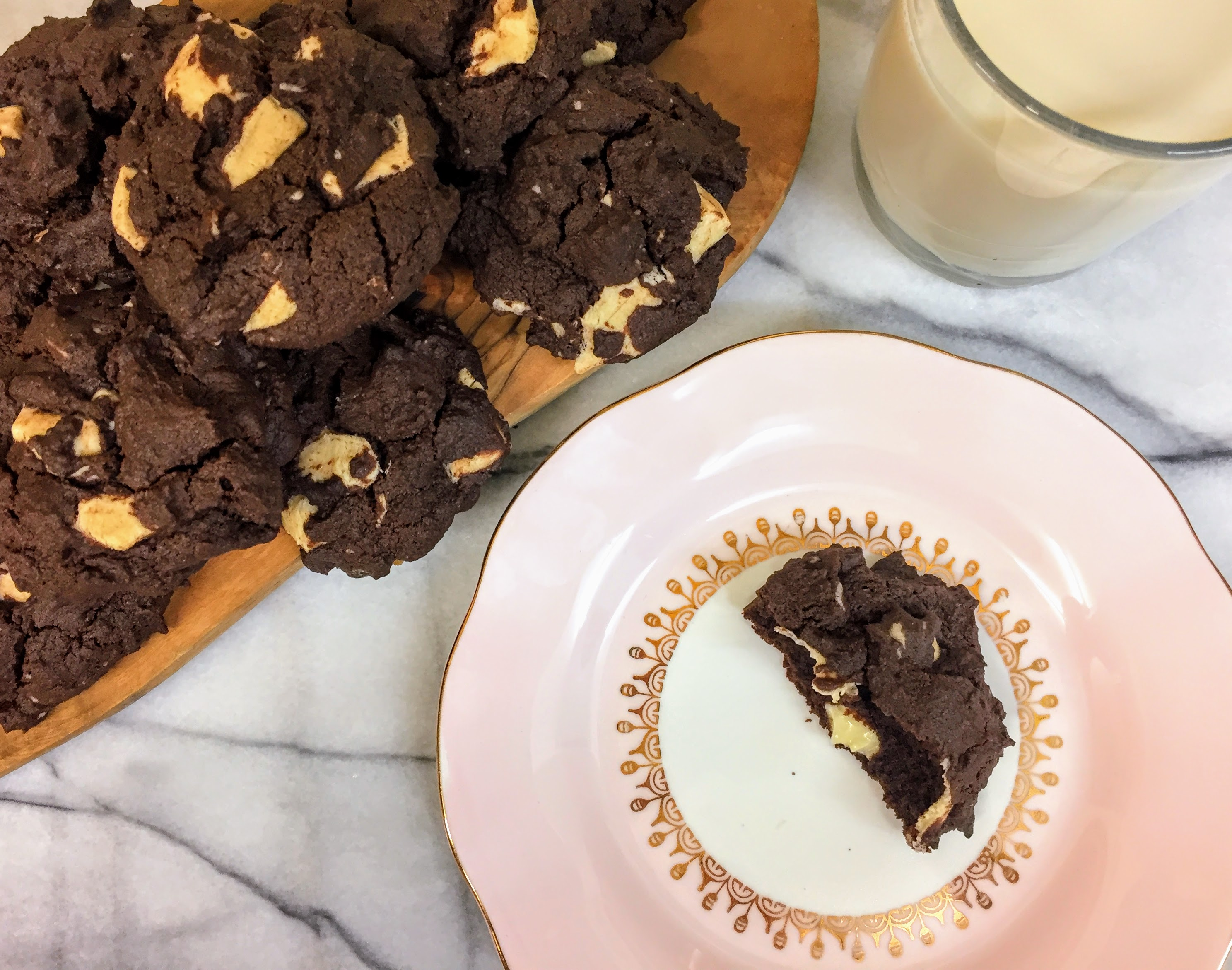 Half a double chocolate brownie cookie on a pink plate, with the remaining cookies in a pile to the left, next to a glass of non-dairy milk.