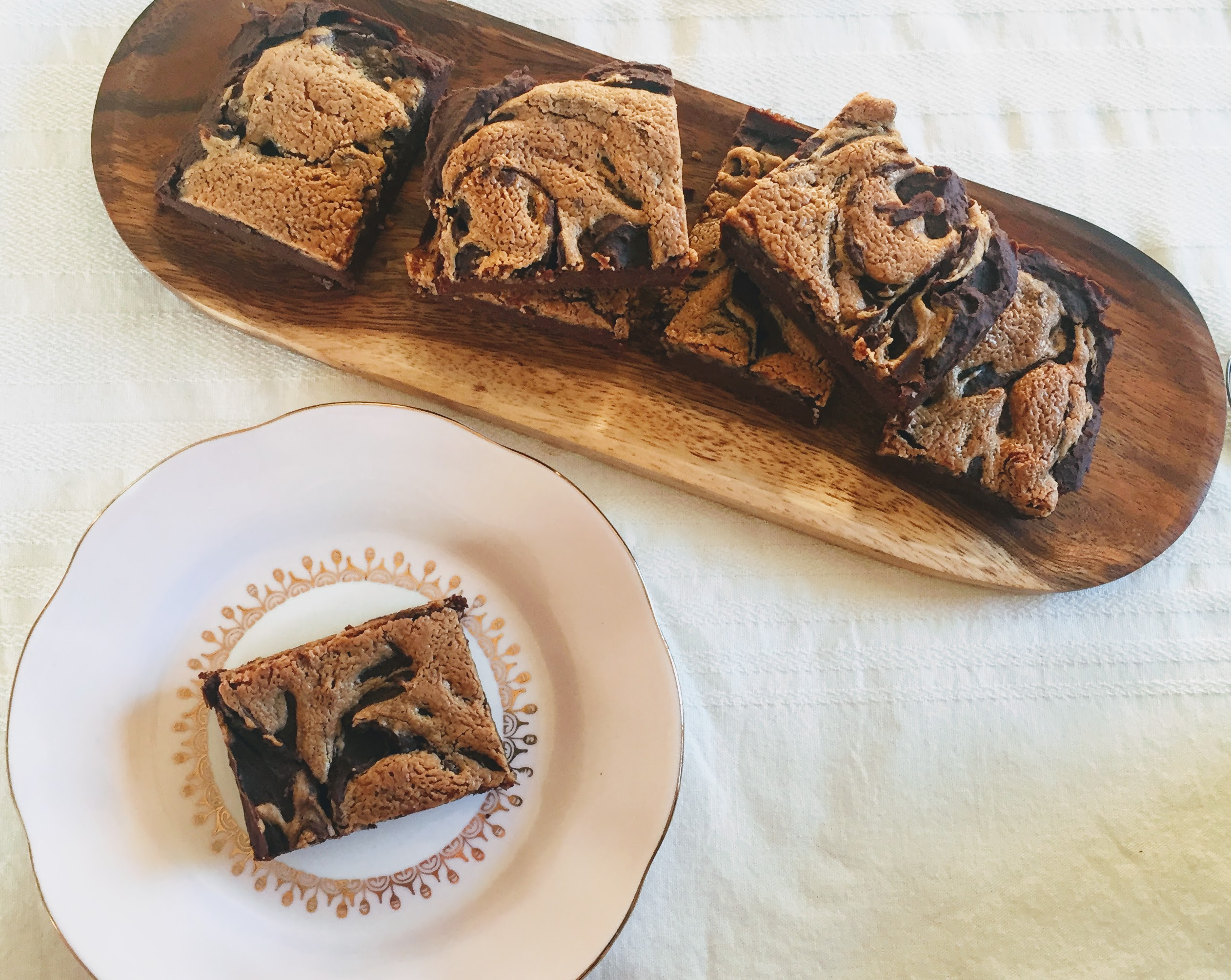 An aerial view of the peanut butter, banana and chickpea brownies. One is on a plate and the others are on a wooden board. You can see the golden peanut butter swirl topping contrasted with the deep, dark chocolate of the brownies.