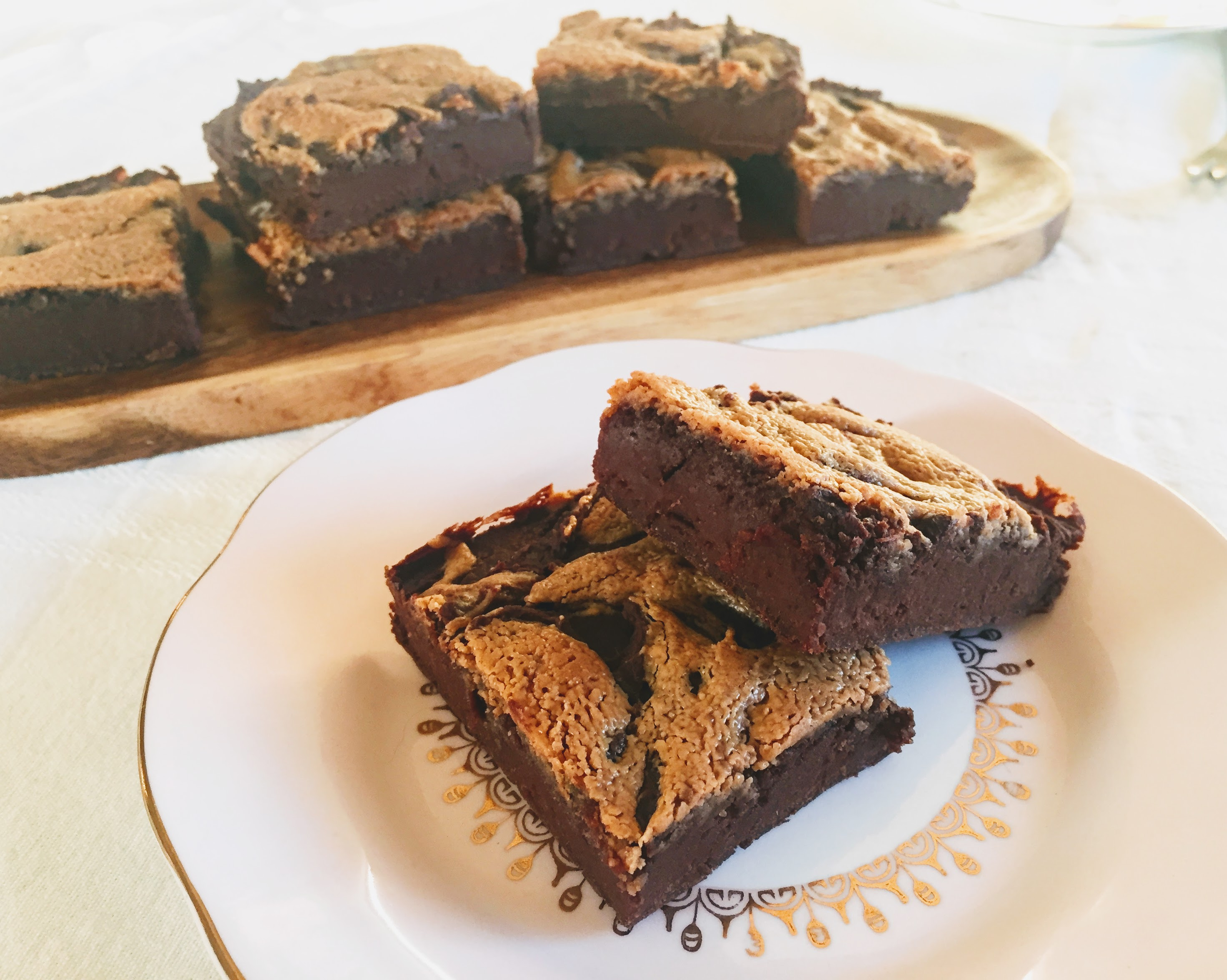 Two dark and fudgy brownies stacked on a pink place. Each has golden-coloured swirls of peanut butter on top, and the remaining brownies are on a platter in the background.