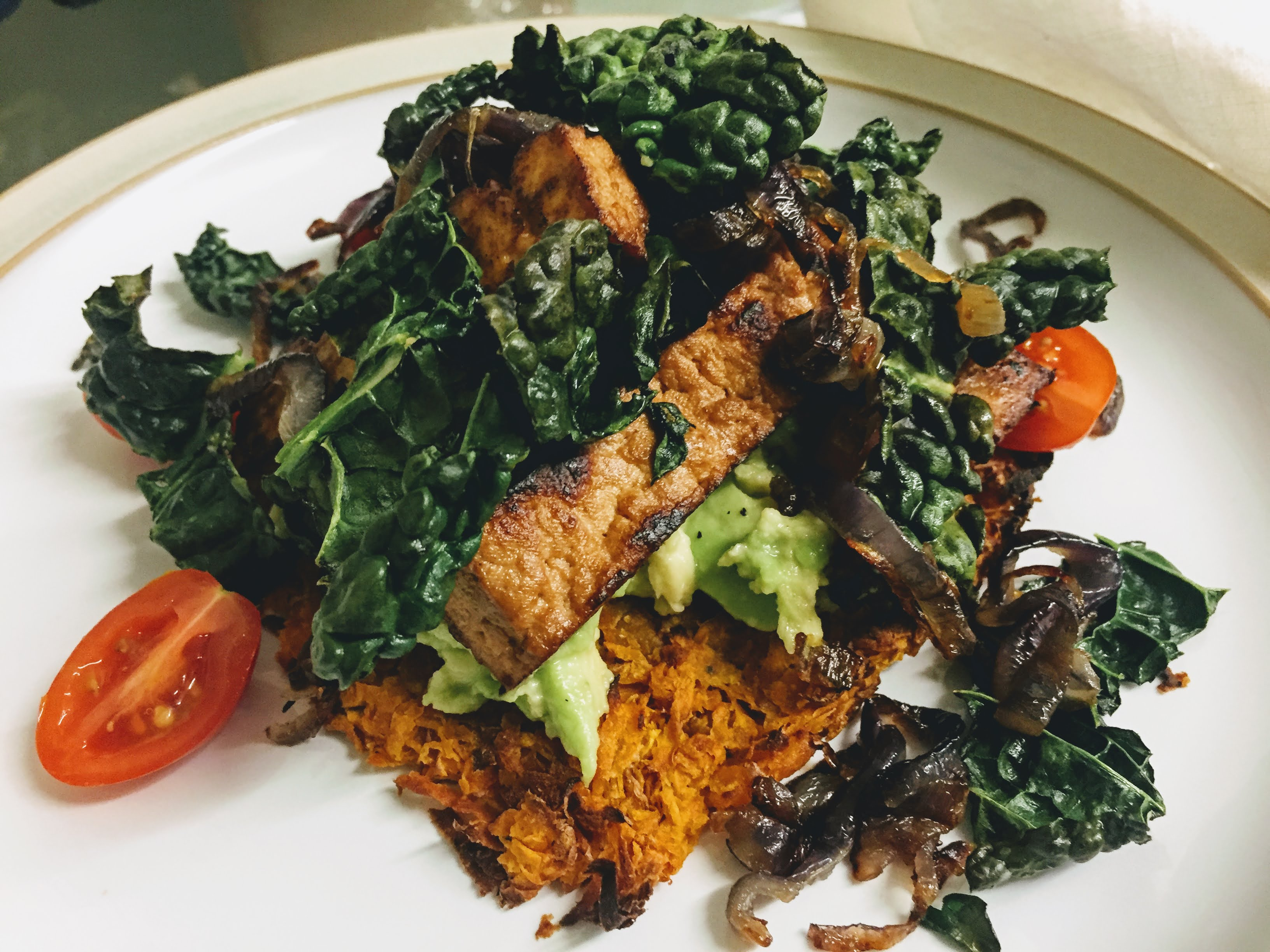 A side view of the finished dish. The sweet potato rösti is at the base, it's edges blackened slightly, and smothered in creamy smashed avocado. The fried tofu is nestled on top and everything is scattered with crispy kale and fried onions, with some cherry tomatoes peaking out.