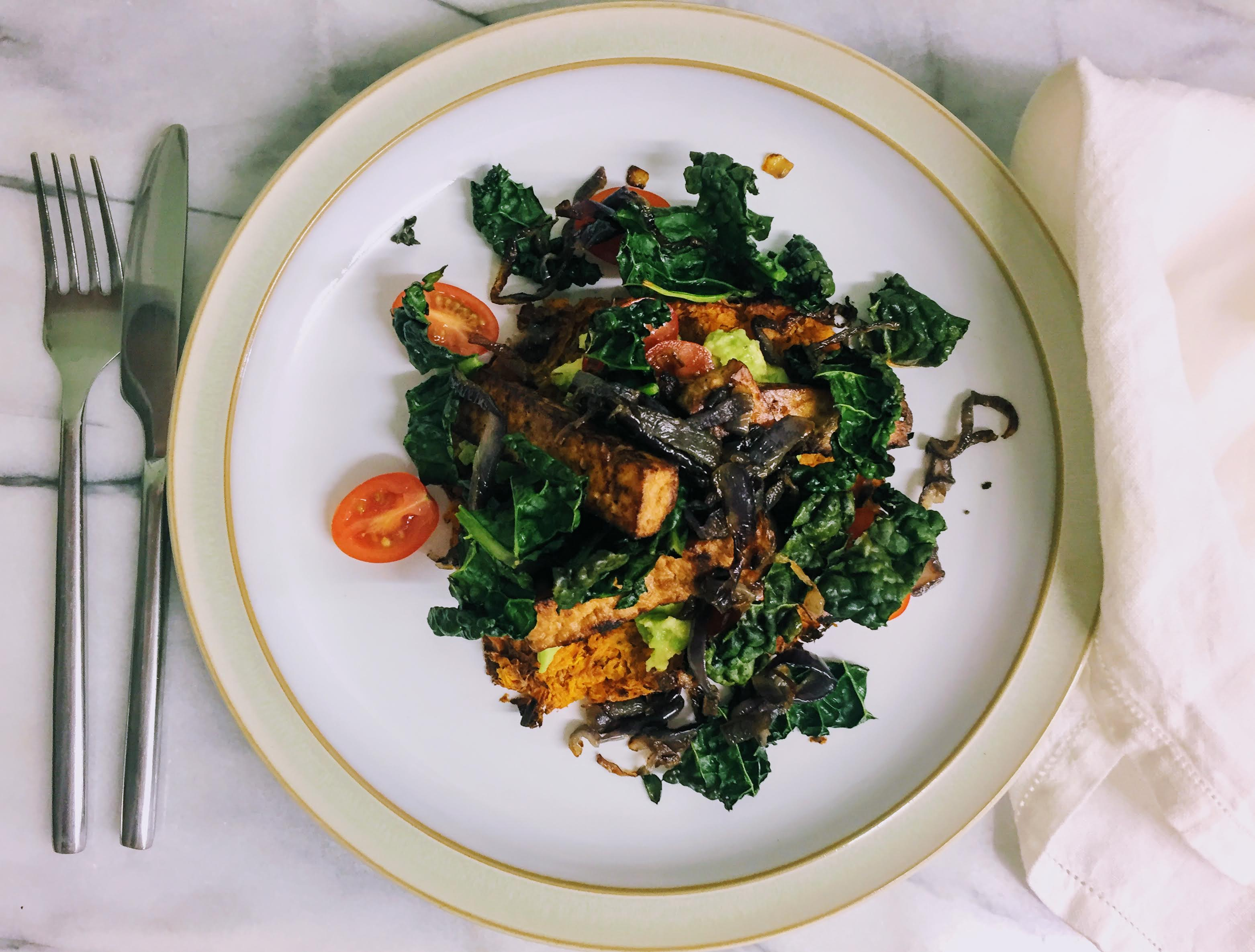 A white plate, photographed from above, with a tangle of dark green kale, caramelized red onions, cherry tomatotes, and charred batons of smoked tofu. There are flashes of lime green smashed avocado and the vibrant orange of the sweet potato rosti peaking out from underneath