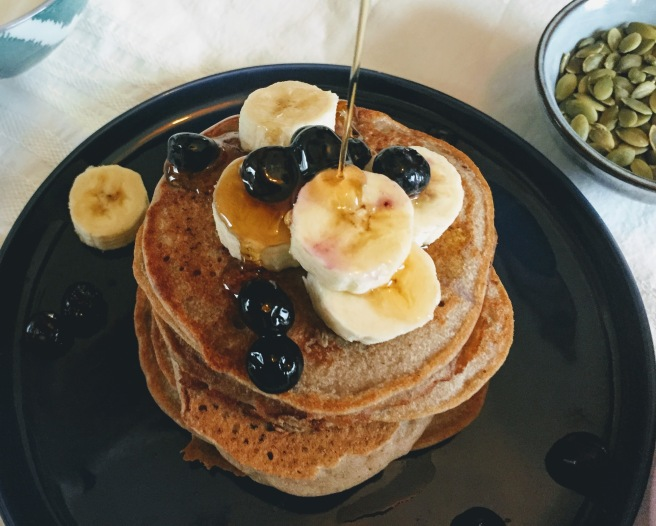 A stack of buckwheat, banana and cinnamon pancakes, piled with sliced banana and blueberries, with a stream of shiny amber maple syrup cascading over the fruit and dripping  down the side of the pancakes.