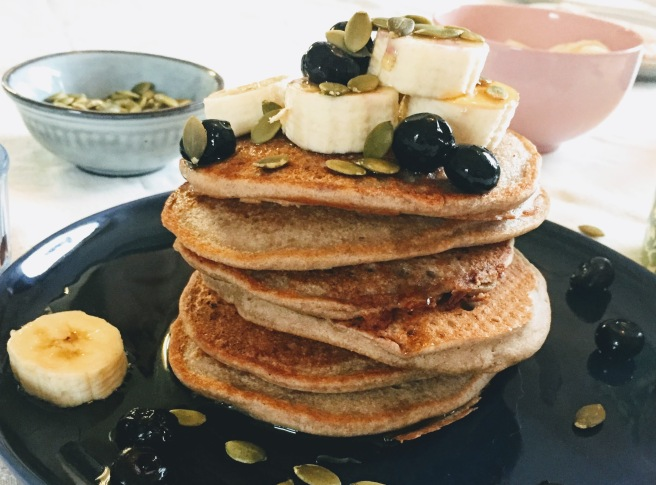 Buckwheat, banana and cinnamon pancakes shown from the side. There are six fat, golden brown pancakes in a wonky stack, sitting in a pool of maple syrup, with banana slices, blueberries and pumpkin seeds precariously piled on top.