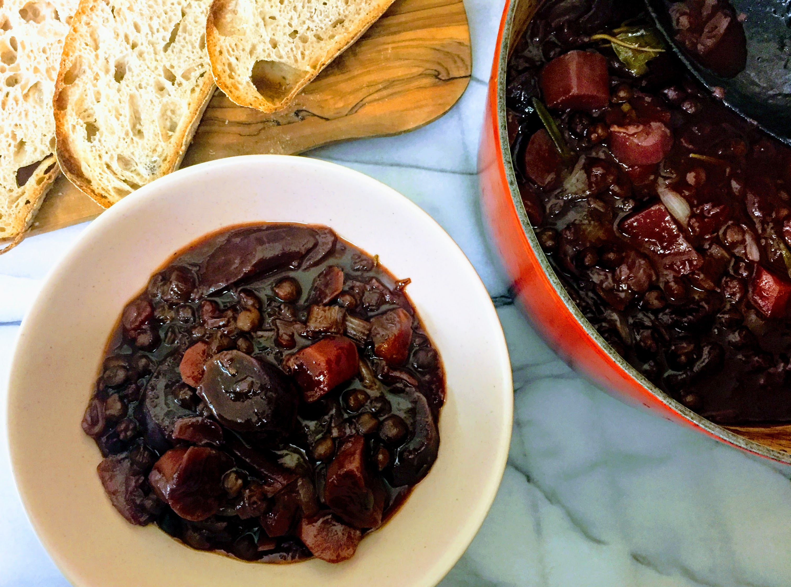 A bowl of chickpeas au vin seen from above. The stew has an intensely dark red wine colour, an there are large chunks of purple carrots surrounded by chickpeas, all drenched in smooth, dark and glossy gravy. To the right is the casserole dish the remaining stew, and at the top there are some thick slices of sourdough bread on a wooden board.