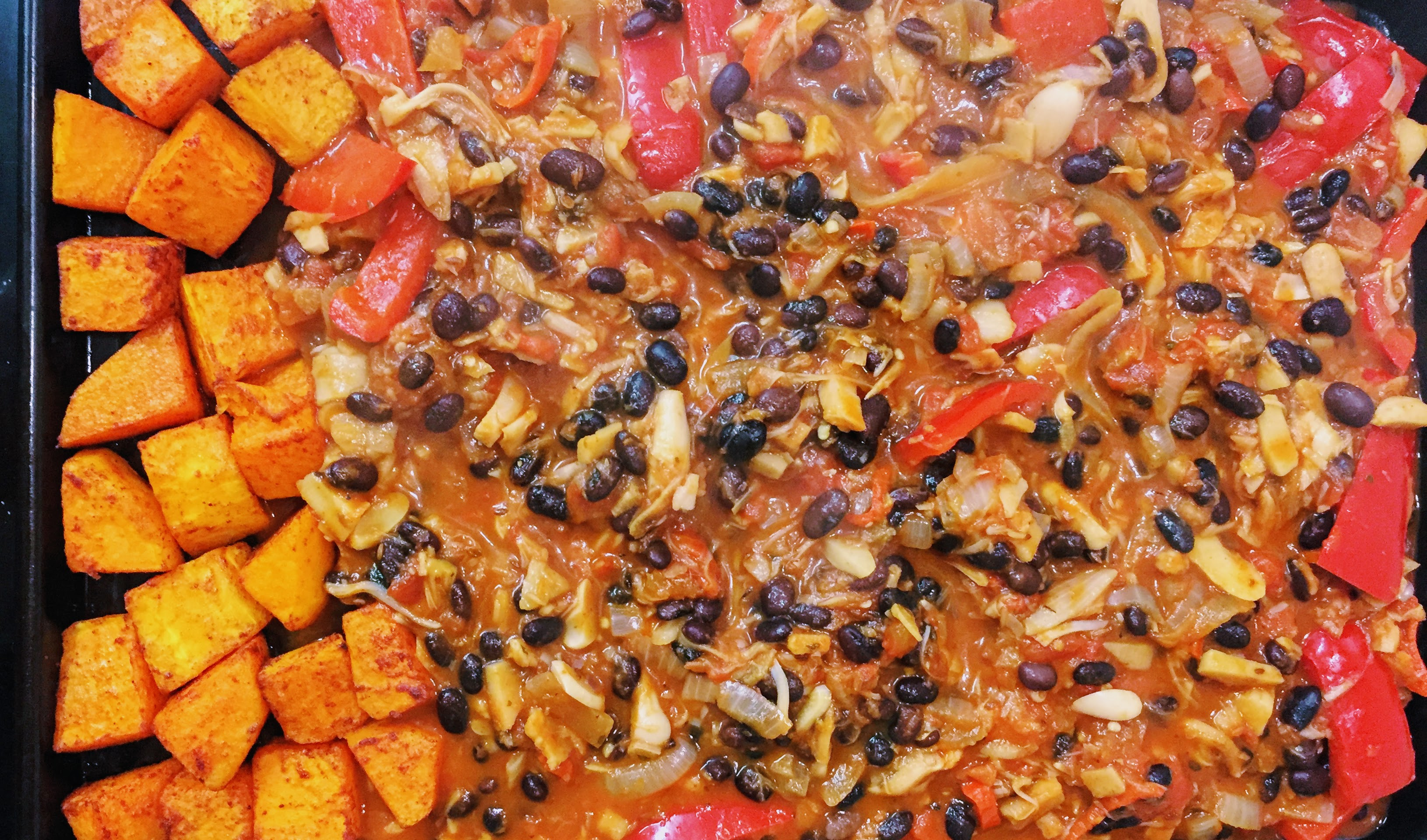 A baking tray with vibrant chunks of butternut squash on one side, and the steaming hot chilli mixture spread out across the rest of the tray.