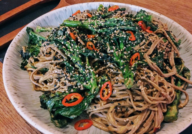 A close up of the noodles - soba noodles have a darker colour than regular noodles due to the added buckwheat. The noodles are shiny with sesame sauce, and the cooked purple sprouting leaves have turned an even darker green, next to the vibrant broccoli stalks.