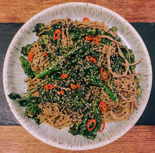 A large plate covered in a tangle of soba noodles and dark green spears of purple sprouting broccoli. Everything is coated in a creamy sesame sauce, and the entire thing is scattered with white and black toasted sesame seeds and bright flecks of red chilli.