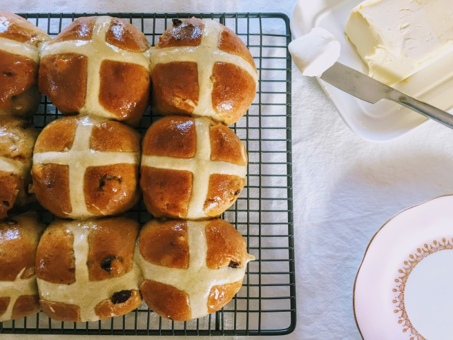Shiny, golden brown hot cross buns on a wire cooling rack, ready to be savoured.