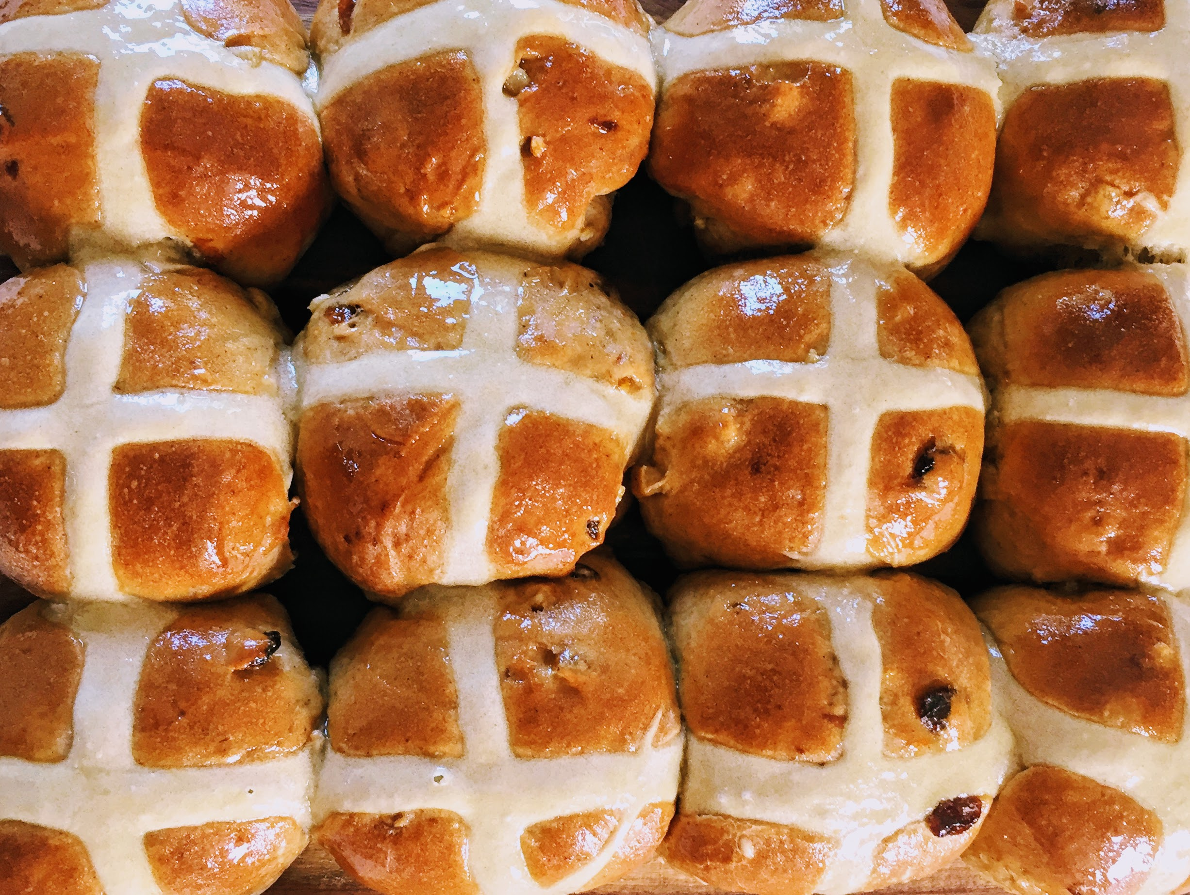 A close-up of twelve hot cross buns  -they are beautifully golden brown on top with a white cross on each, and there are hints of sultanas peeking through the dough. The buns are glossy with an orange glaze.