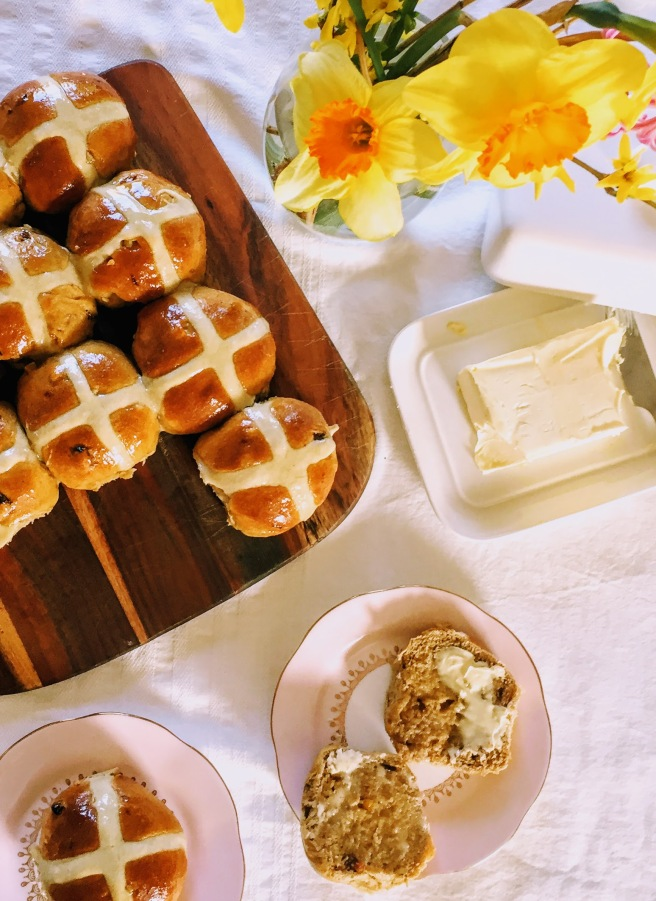 Shiny hot cross buns, served on a wooden board. There's a vase of bright yellow daffodils at the top of the picture, an open butter dish, and two hot cross buns on dainty pink plates, one of which has been cut in half and spread with lashings of butter.
