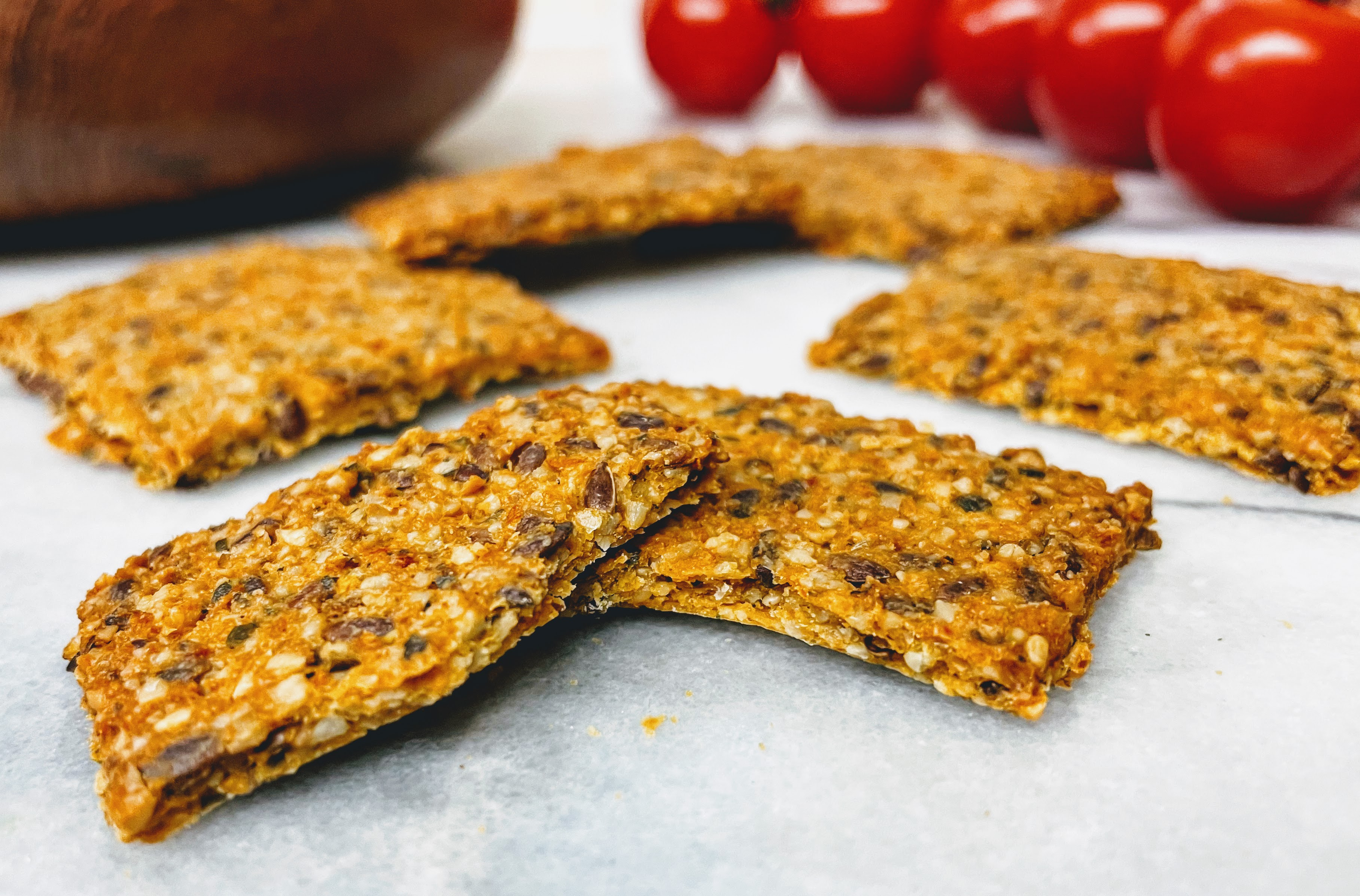 A closer view of a sun-dried tomato cracker snapped in half. The crackers are super thin and a little flaky, with chopped seeds and a few brown flax seeds left whole.