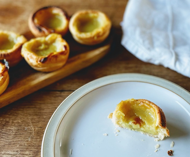 A pastel de nata sliced in half to reveal the smooth and silky set custard, surrounded by flaky puff pastry.