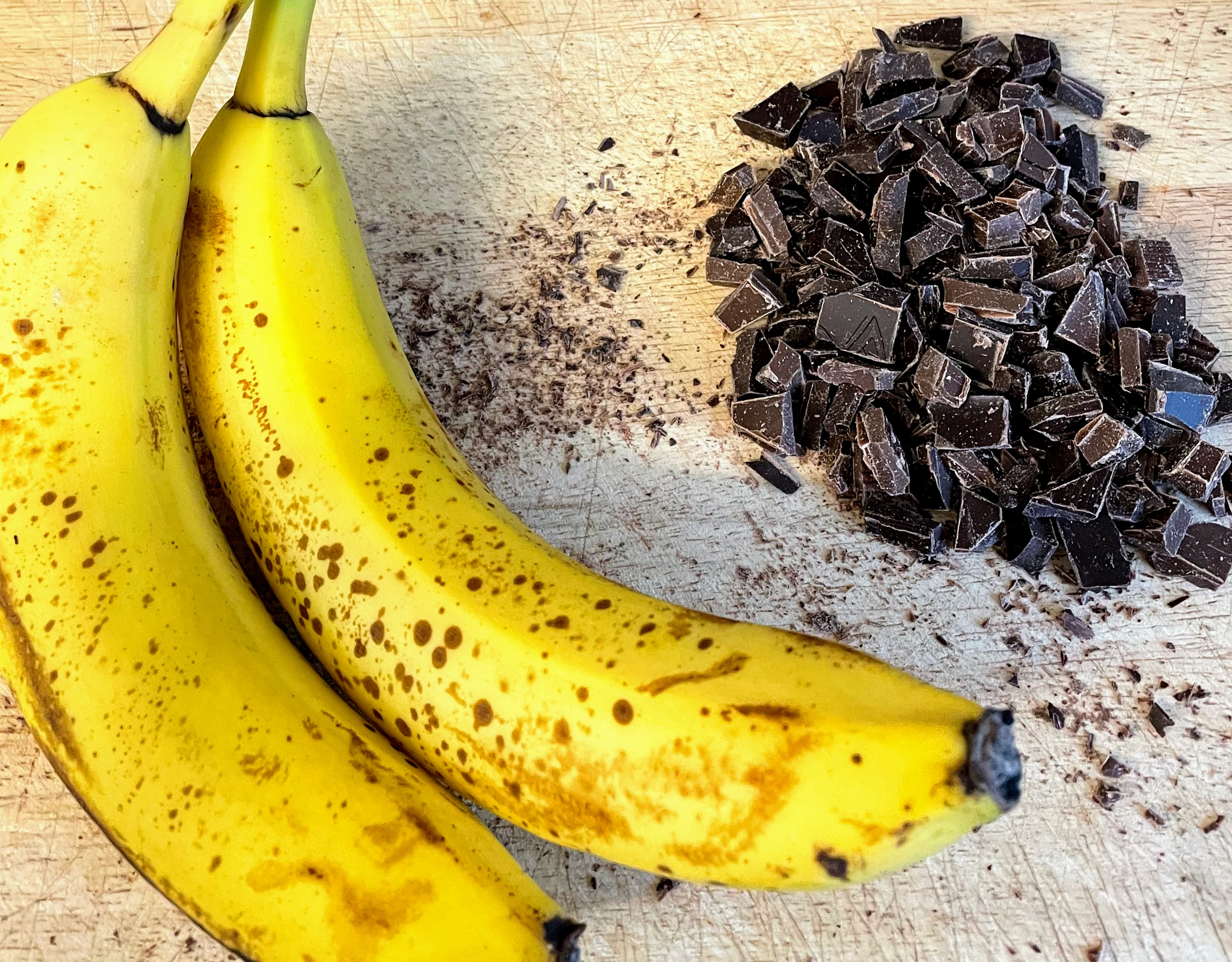 My bananas - still mostly yellow but with a decent number of brown spots - next to a pile of chopped dark chocolate.