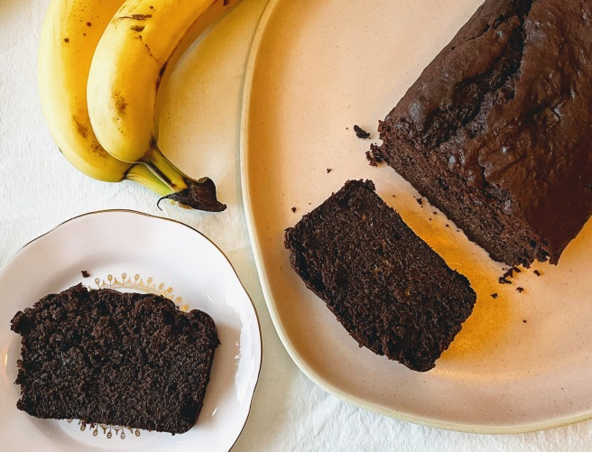 An aerial view of the sliced loaf of chocolate buckwheat banana bread. One slice remains on the plate next to the loaf, and the other is on a side plate nearby. There are a few dark chocolate crumbs and two bananas at the top left of the picture.