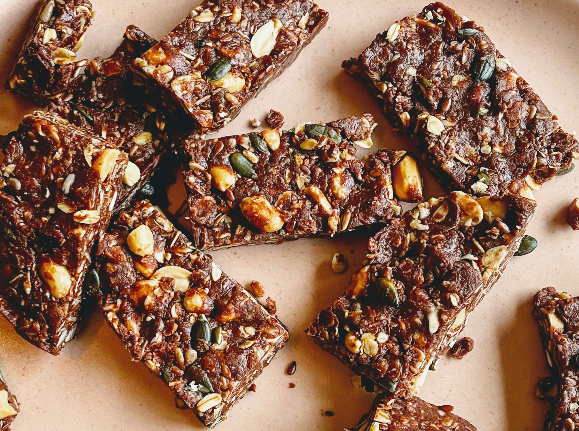 Chocolate and peanut protein bars arranged haphazardly on a pink plate. The bars are a dark chocolatey brown, with a messy mosaic of oats, peanuts, and mixed seeds peeking through.