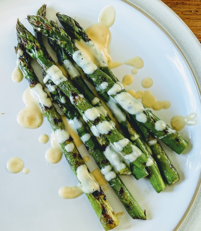 A few spears of grilled asparagus on a white plate, generously and messily drizzled in white miso hollandaise. The asparagus spears are bright green and charred black in places, and the sauce is pale yellow, thick and silky smooth.