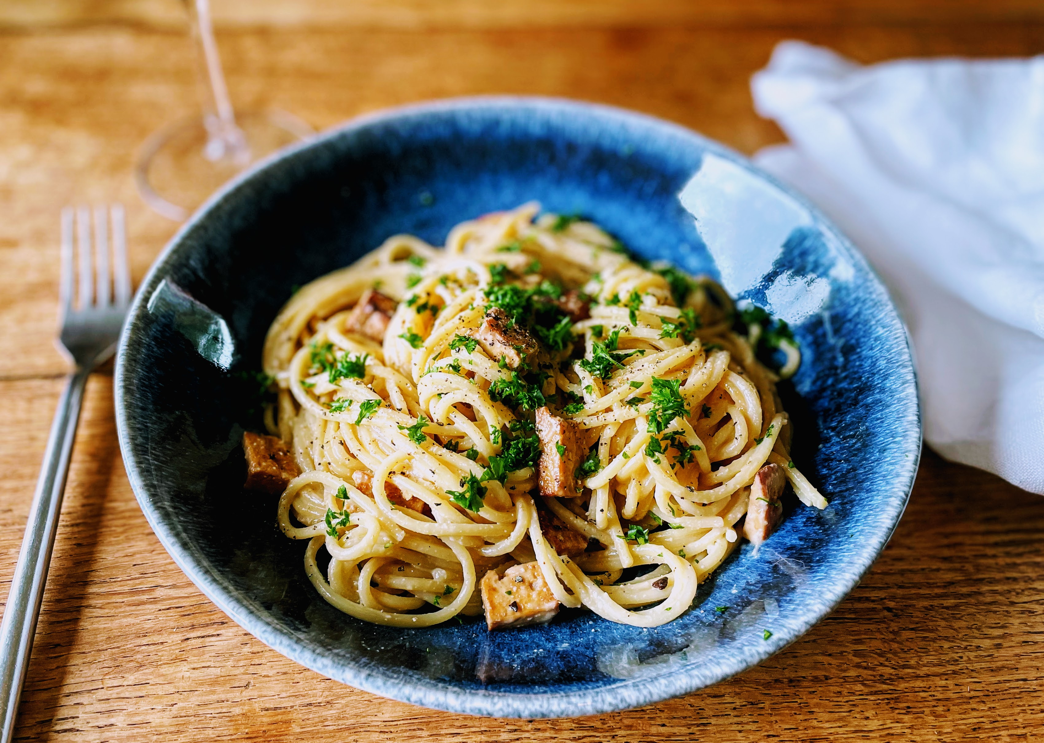 A dark blue shallow bowl piled with a tangle of creamy spaghetti, with little bits of crisp, marinated smoked tofu. There's a sprinkling of chopped fresh parsley on top.