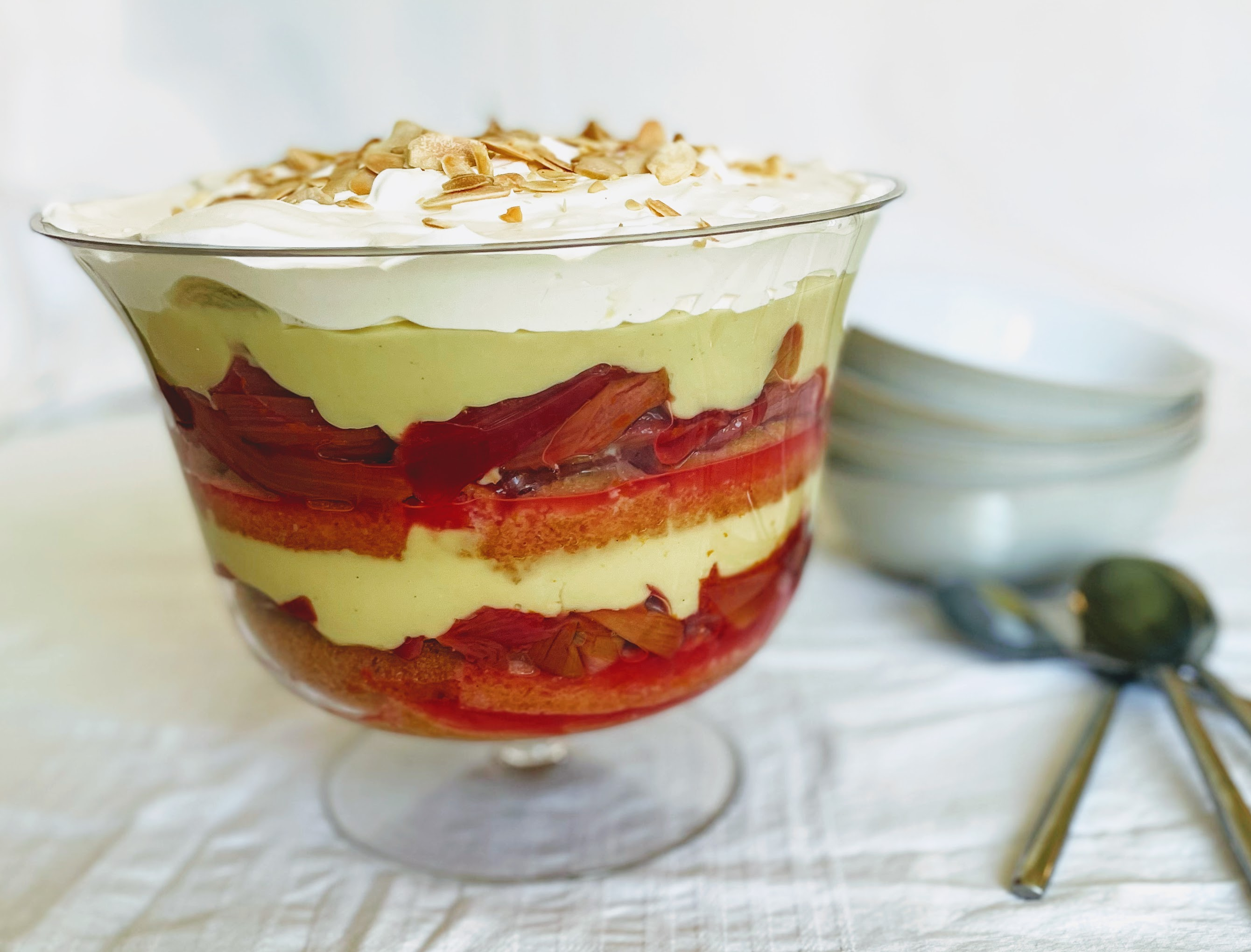 The rhubarb and custard trifle, with layers of golden sponge, vibrant pink rhubarb, creamy yellow custard, and light pillows of vegan whipped cream. There are serving bowls and spoons in the background.