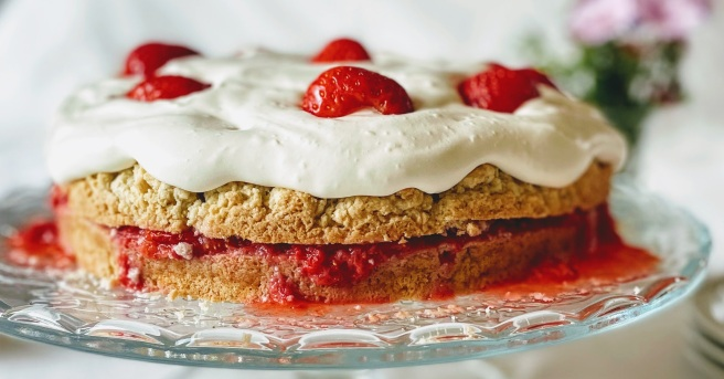 A closer, side-on view of the strawberry shortcake. The shortcake is light golden-brown and slightly rough in texture, and you can see that some of the juice from the crushed strawberry filling is starting to seep into the bottom layer of cake. The vegan whipped cream is piled on top, with a few jewel-red strawberry halves for decoration.