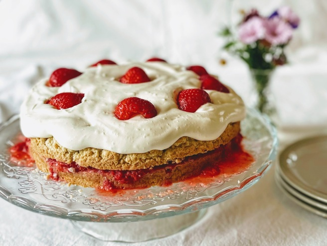A strawberry shortcake on a glass cake stand.  The shortcake is pale golden brown, and sliced in half, with bright red crushed strawberries oozing out of the side. The top is slathered with soft and pillow-y whipped cream and dotted with bright and shiny strawberry halves. There are some side plates next to the cake stand, and a vase with pink and purple flowers in the background.