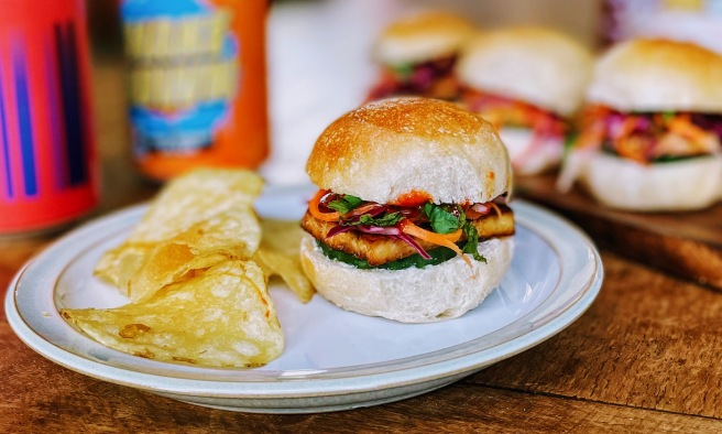 A banh mi slider on a side plate with some crisps. The bun is a beautiful golden brown on top and soft in the middle. You can see a slice of fried tofu peaking out with charred, crispy edges, underneath a tangle of vibrant carrot and red cabbage pickle and soft herbs. A little sploodge of bright red sriracha hints at the spicy filling. In the background are a couple of cans of beer and three more sliders on a wooden boards.