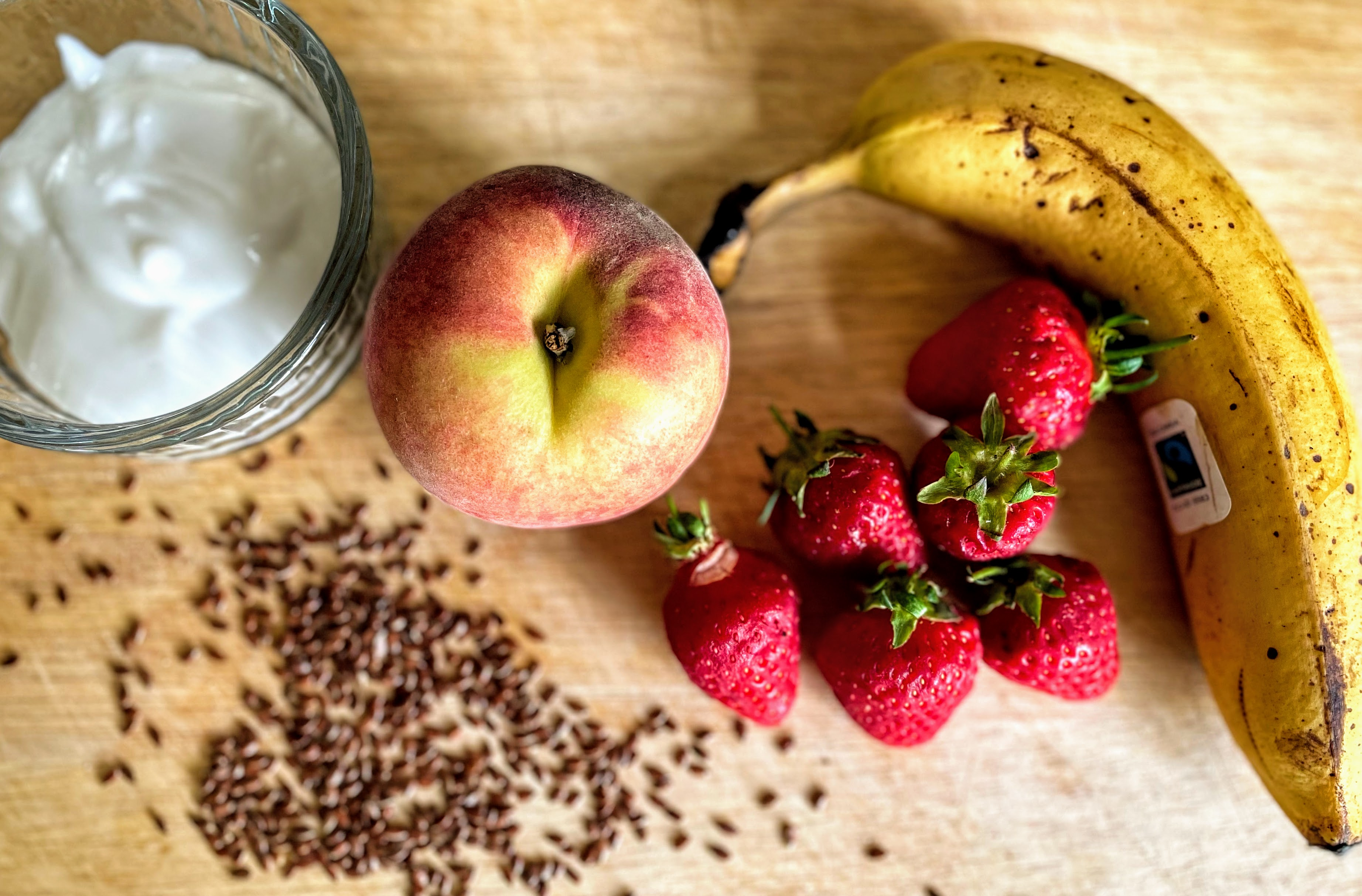 A chopping board with some of the ingredients - an overripe banana, a handful of strawberries, a peach, some coconut yogurt and a scattering of flax seeds.