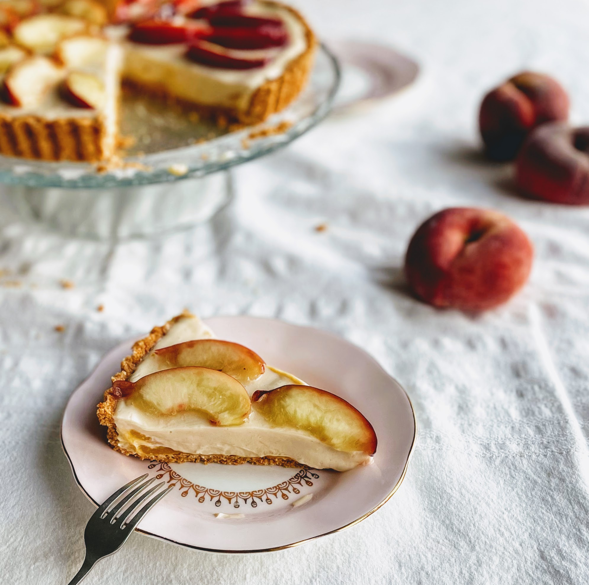 A slice of peach and white chocolate tart. The base is thin and crisp and you can see a bright flash of peach puree underneath the silky smooth white chocolate filling. There are three juicy slices of fresh peach on top, and three velvety peaches in the background, along with the rest of the tart on a glass cake stand.