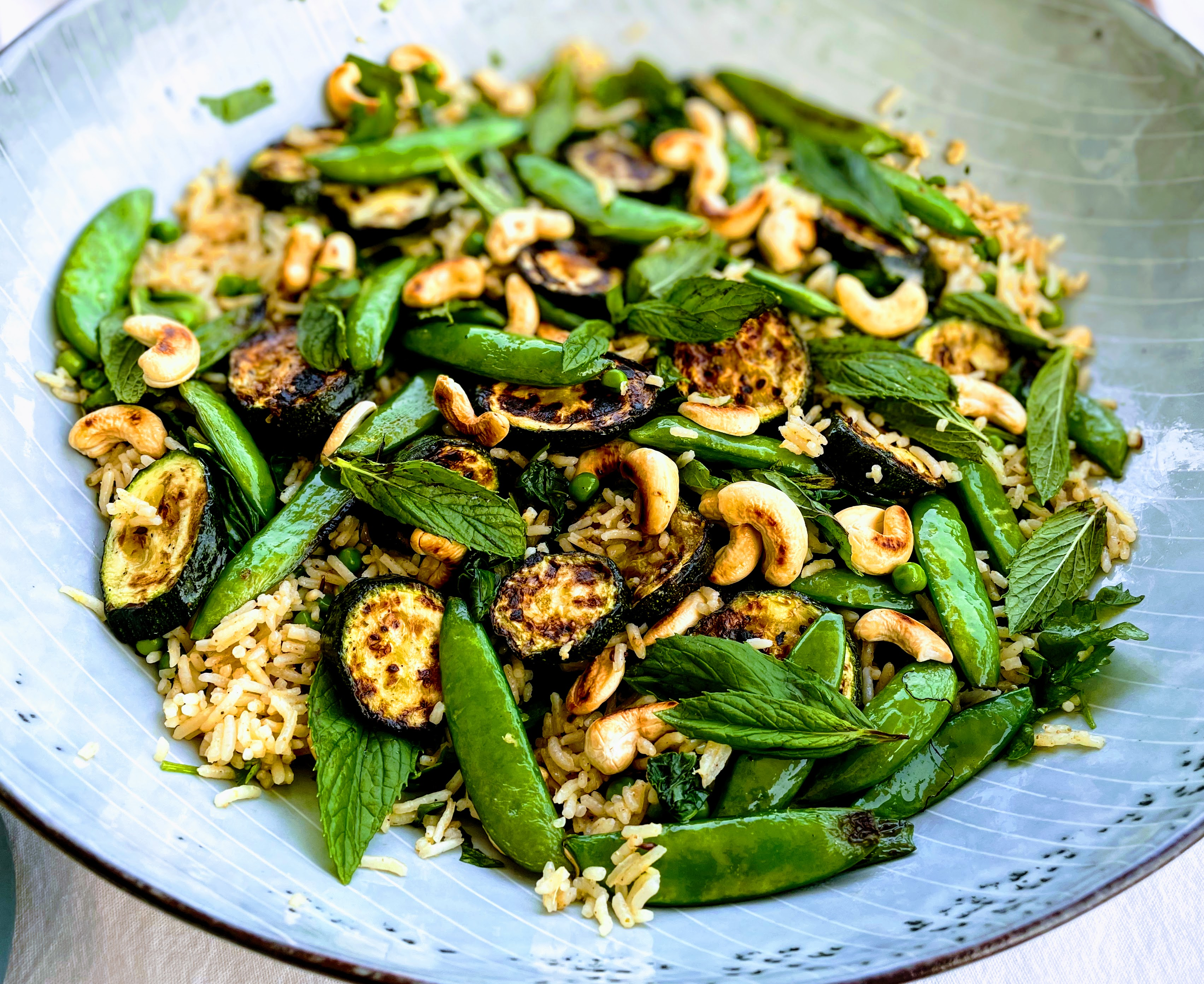 A closer view of the Indian rice salad with summer vegetables. The rice is dotted with peas and coriander, and the courgettes and sugar snap peas are gently charred from the BBQ grill. Everything is scattered with toasted cashews and bright green mint leaves.