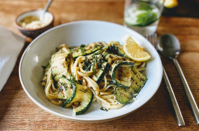 A white pasta bowl filled with a tangle of linguine and grilled slices of courgette. The courgette slices have scorch lines from the grill, and are soft, but still with a little rigidity. The pasta has a creamy sauce that clings to it, and is scattered with shredded mint leaves. There's a wedge of lemon on the side.