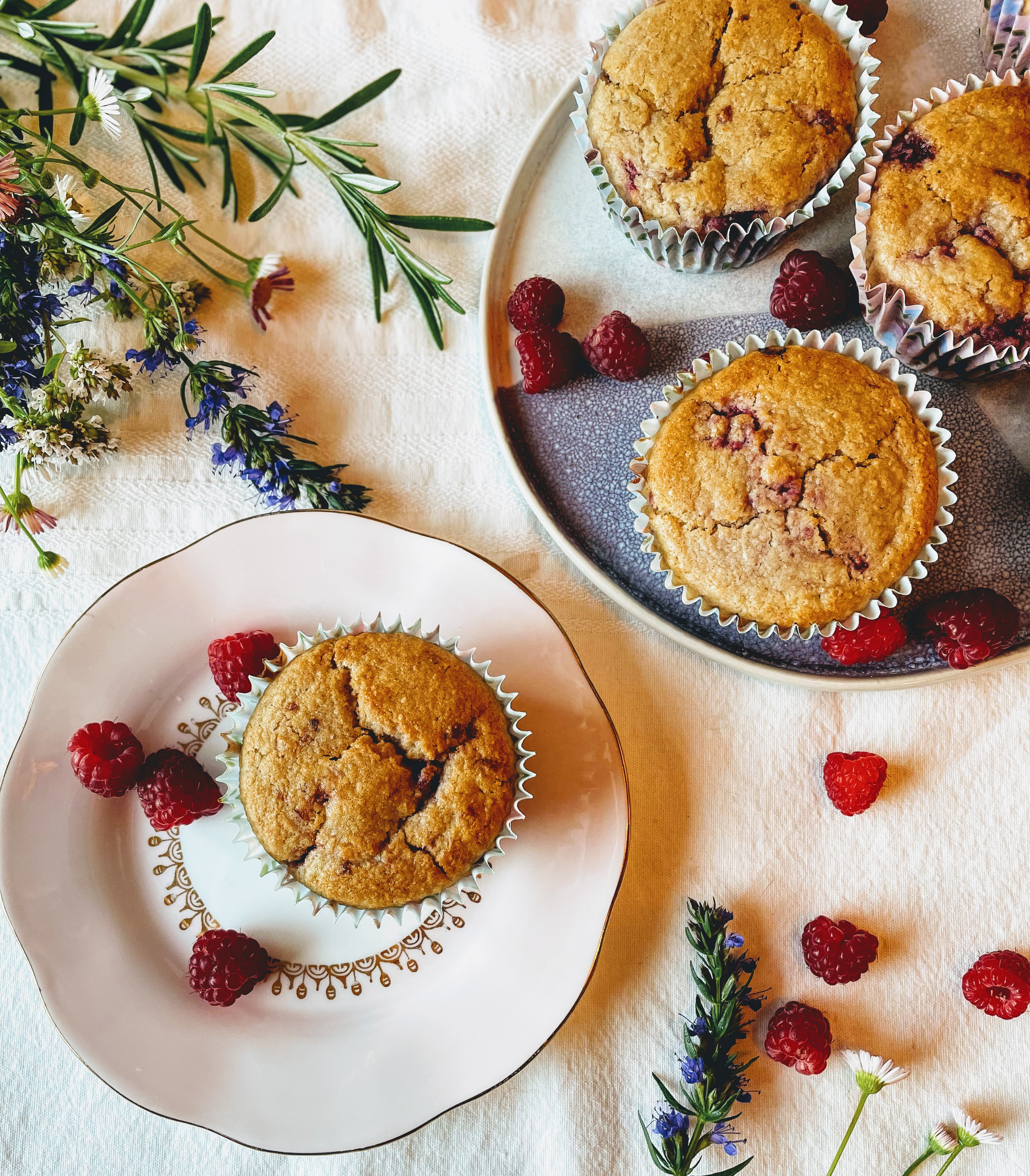A birds-eye view of the lemon and raspberry muffins. One is on a pale pink side plate with a few fresh raspberries scattered next to it, and there are some more muffins on a blue platter at the top right of the picture. All of the muffins are golden brown, with flecks of raspberry peeking through. There are wild flowers, herbs and raspberries scattered on the table cloth next to the plates.