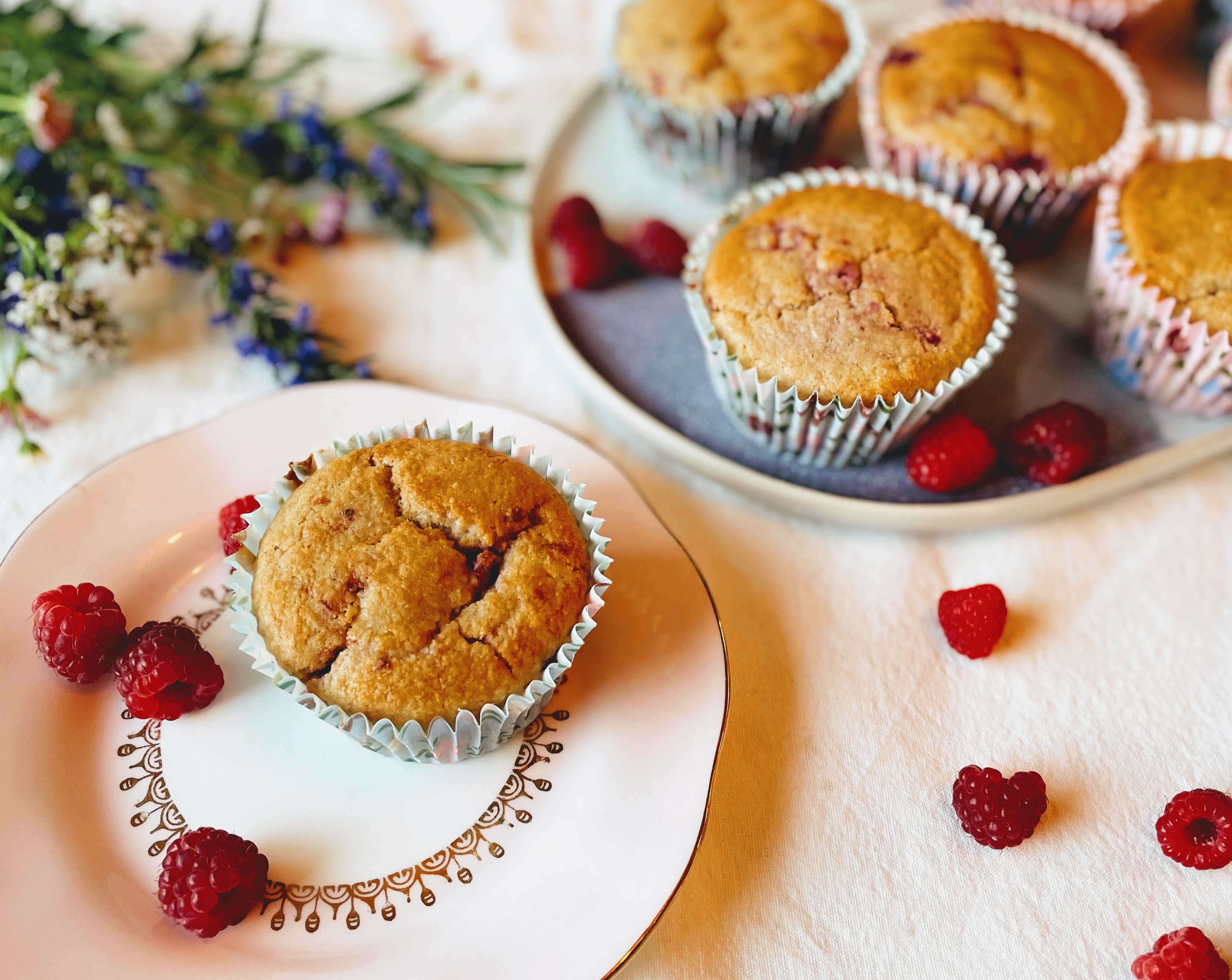 A lemon and raspberry muffin on a light pinks plate, with a few fresh raspberries scattered next to it. The muffins is slightly cracked and golden brown on top, and in a blue floral paper case. In the background is a plate with the res of the muffins, some more fresh raspberries and some wild flowers in pink, white and bright blue.