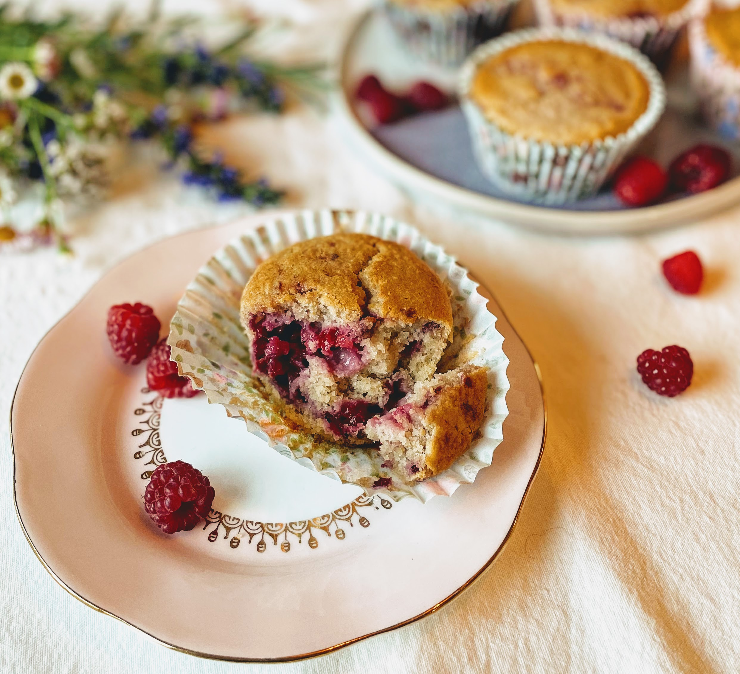 A lemon and raspberry muffin split in half. The sponge is light and delicate, and interspersed with pockets of vibrant and glistening cooked raspberry.